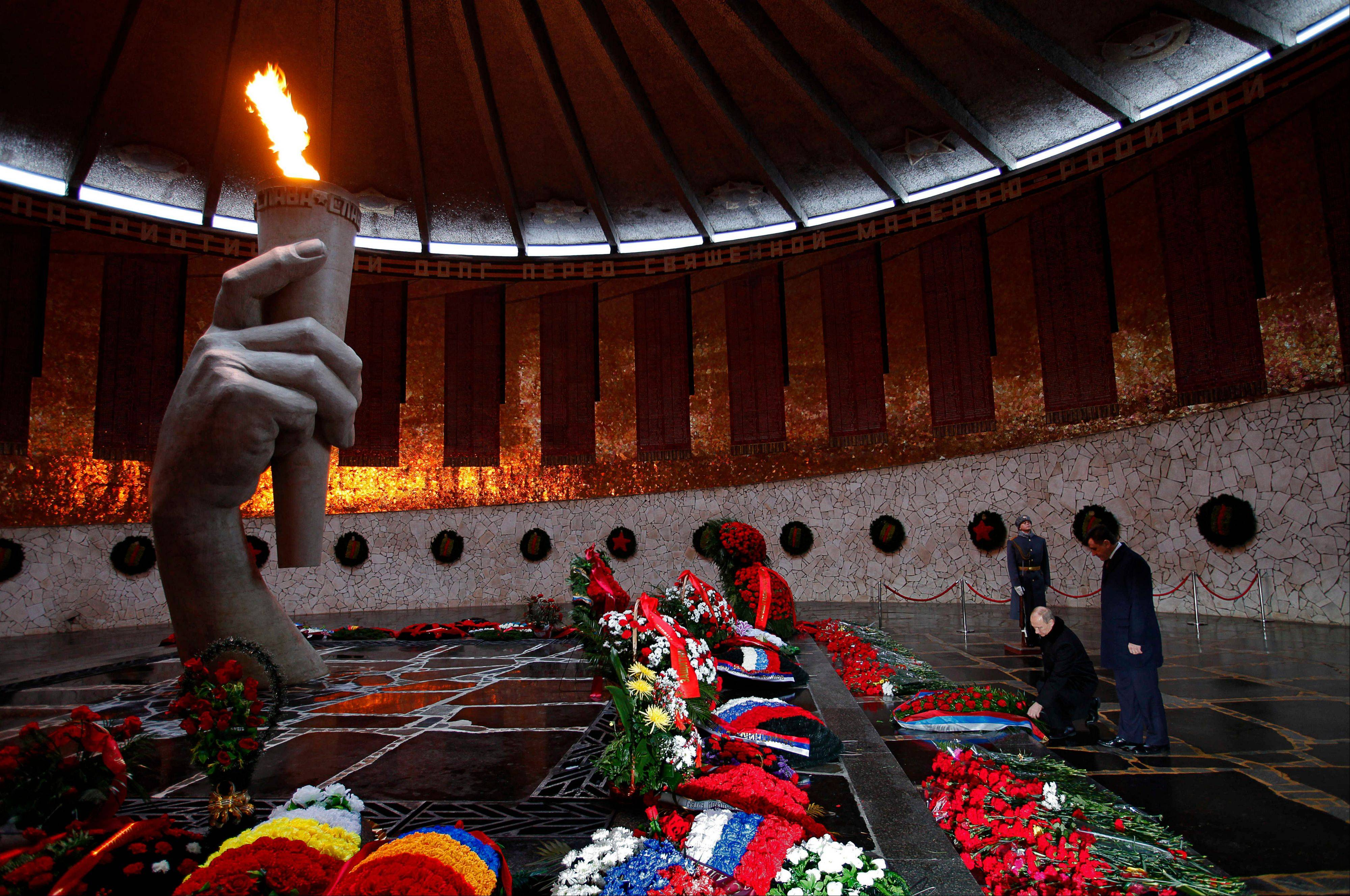 Associated PressPresident Vladimir Putin, second right, lays a wreath at the Eternal Flame as he takes part in ceremonies marking the 70th anniversary of the Battle of Stalingrad.