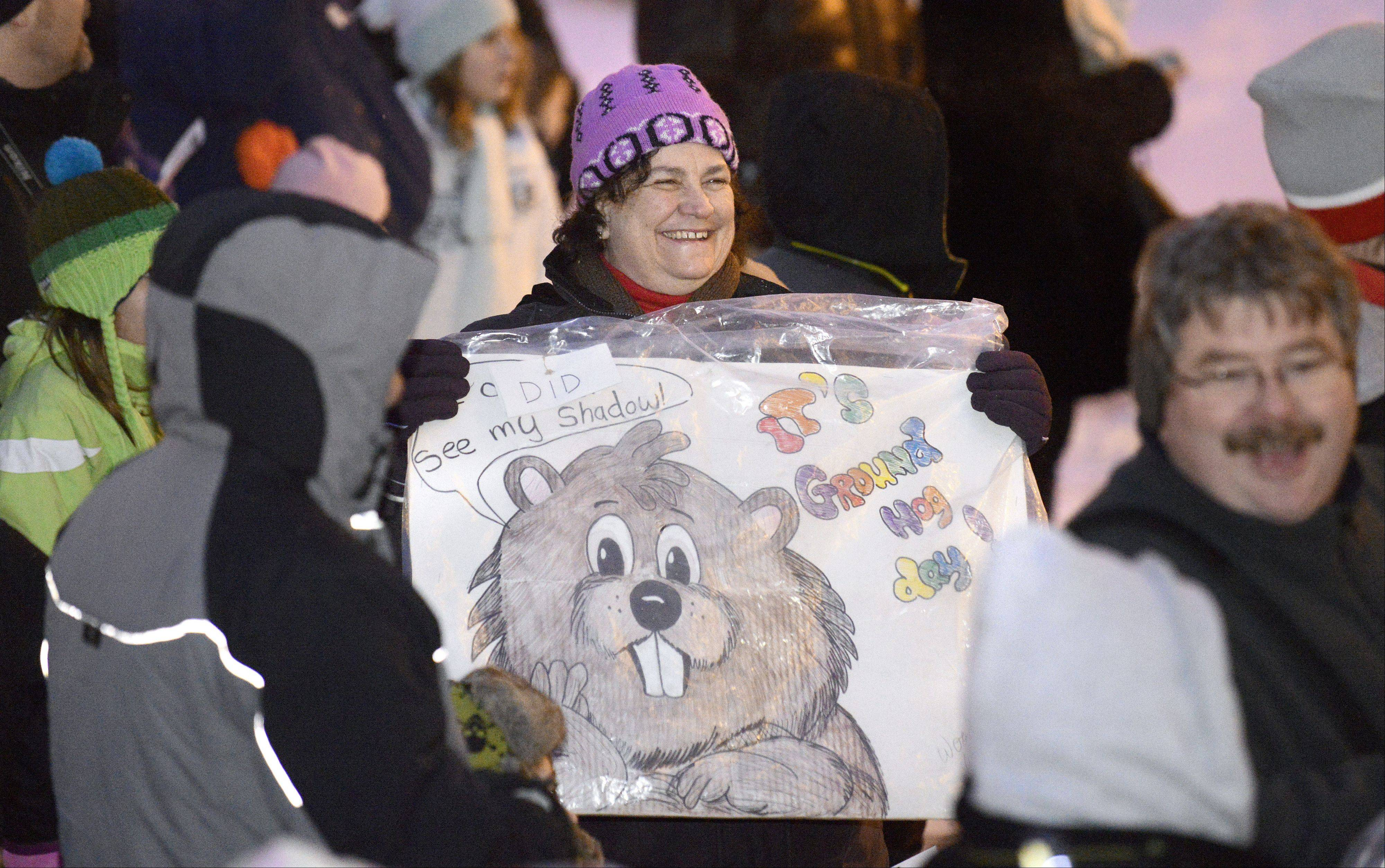 "Sue Carolan of Wonder Lake shows off her Groundhog Day sign before Woodstock Willie makes his appearance and prediction on Saturday. Carolan watched the filming of the movie ""Groundhog Day"" 20 years ago in Woodstock. ""I come every year … It's fun, it's really fun."""