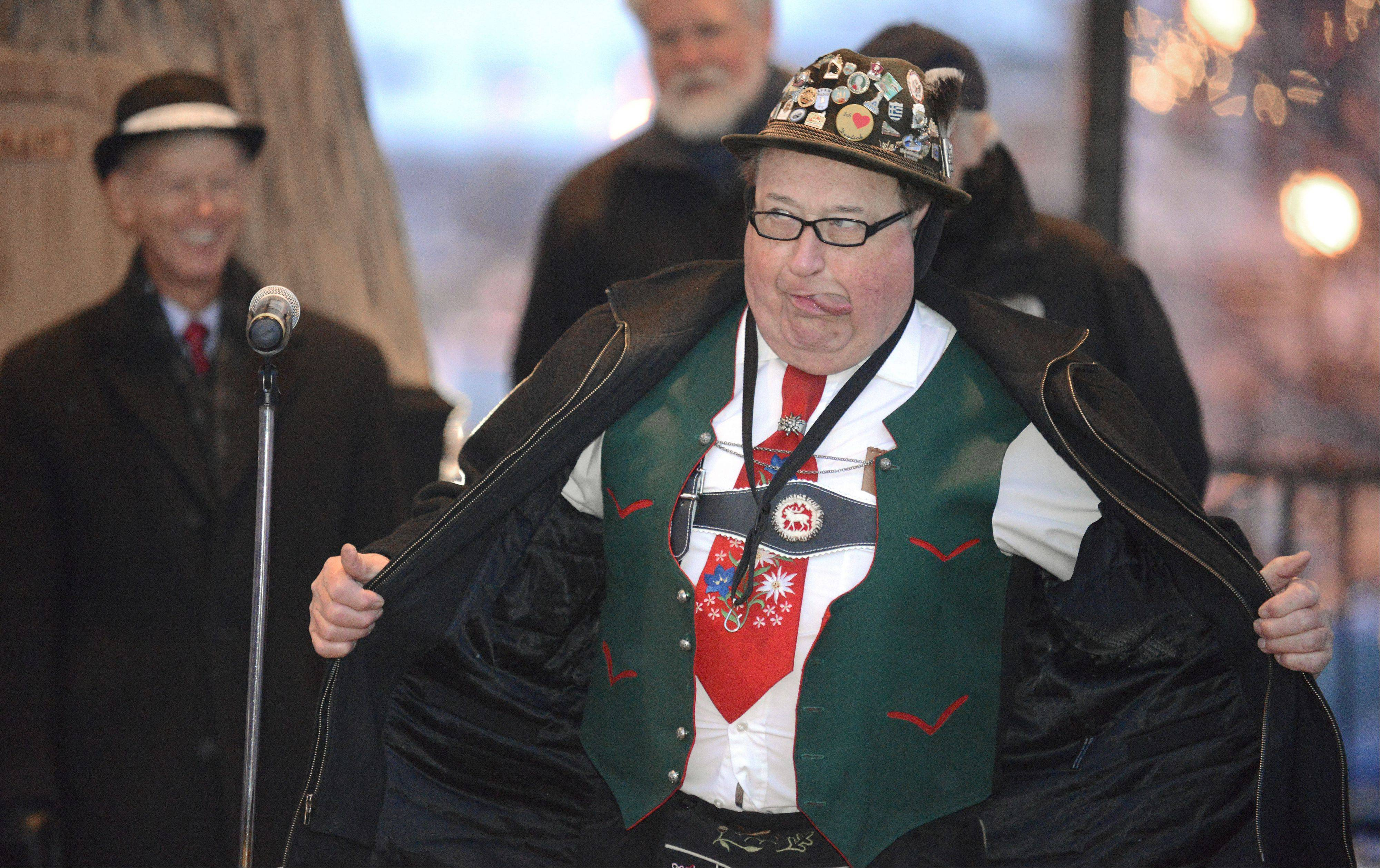 Mike Delaney of Elmhurst, with the German trio music group The Alpiners, gives a quick showing of his lederhosen before bundling up again against the cold at Woodstock's Groundhog Day celebration Saturday. They've performed at the event for eight years.
