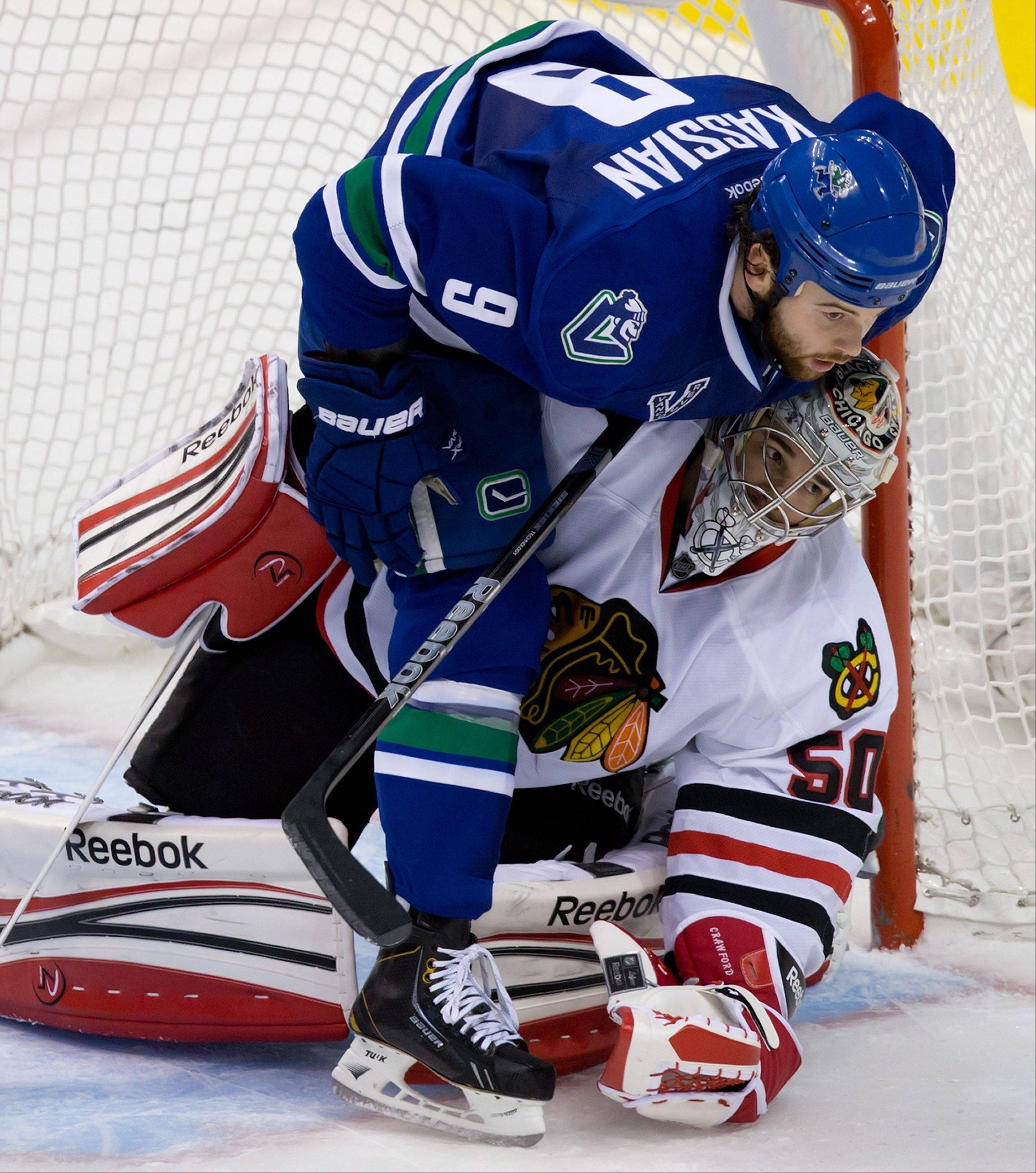 Vancouver Canucks' Zack Kassian, top, falls on Chicago Blackhawks goalie Corey Crawford during the second period of an NHL hockey game in Vancouver, British Columbia, on Friday, Feb. 1, 2013.
