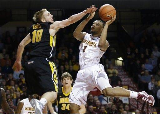 Minnesota�s Andre Hollins, right, lays up as Iowa�s Mike Gesell tries to block the shot in the second half of an NCAA college basketball game on Sunday in Minneapolis. Minnesota won 62-59.