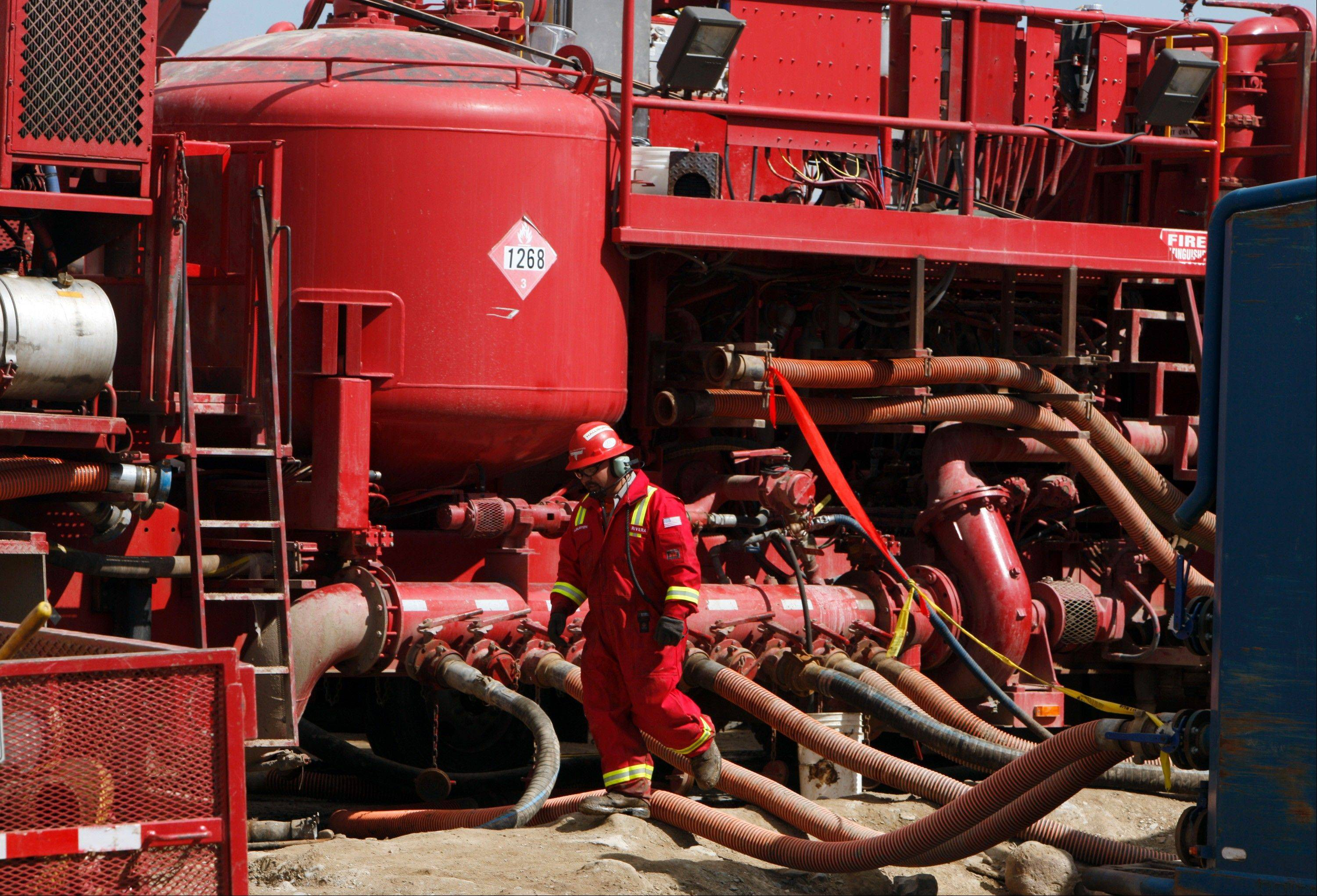In this photo from 2009, a worker steps through the maze of hoses being used at a remote fracking site being run by Halliburton for natural-gas producer Williams in Rulison, Colo. The oil and gas industry is trying to ease environmental concerns by developing non-toxic fluids for the drilling process known as fracking.