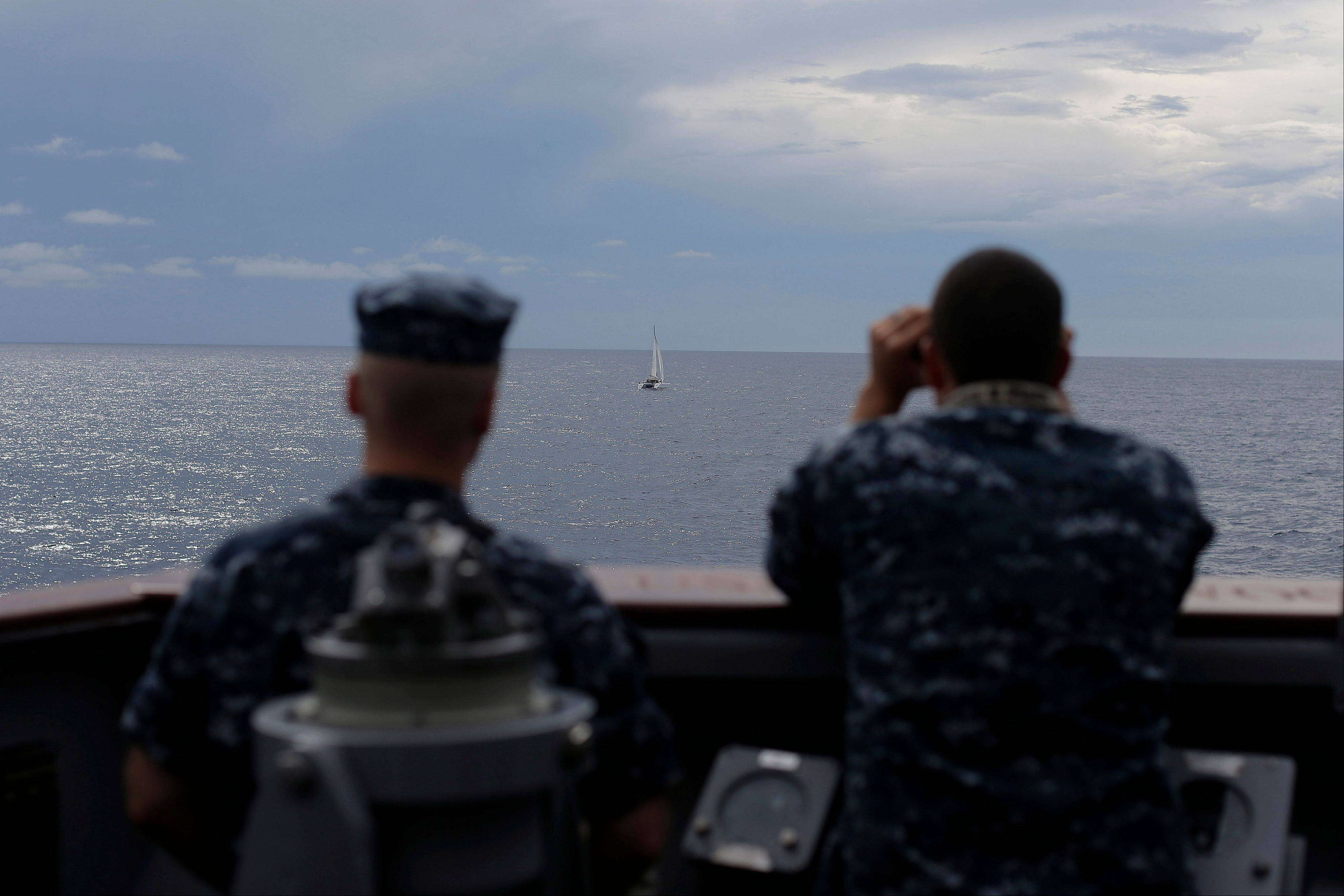 U.S. Navy sailors look out at a small sailing vessel as the USS Underwood prepares to approach them while patrolling in international waters near Panama.