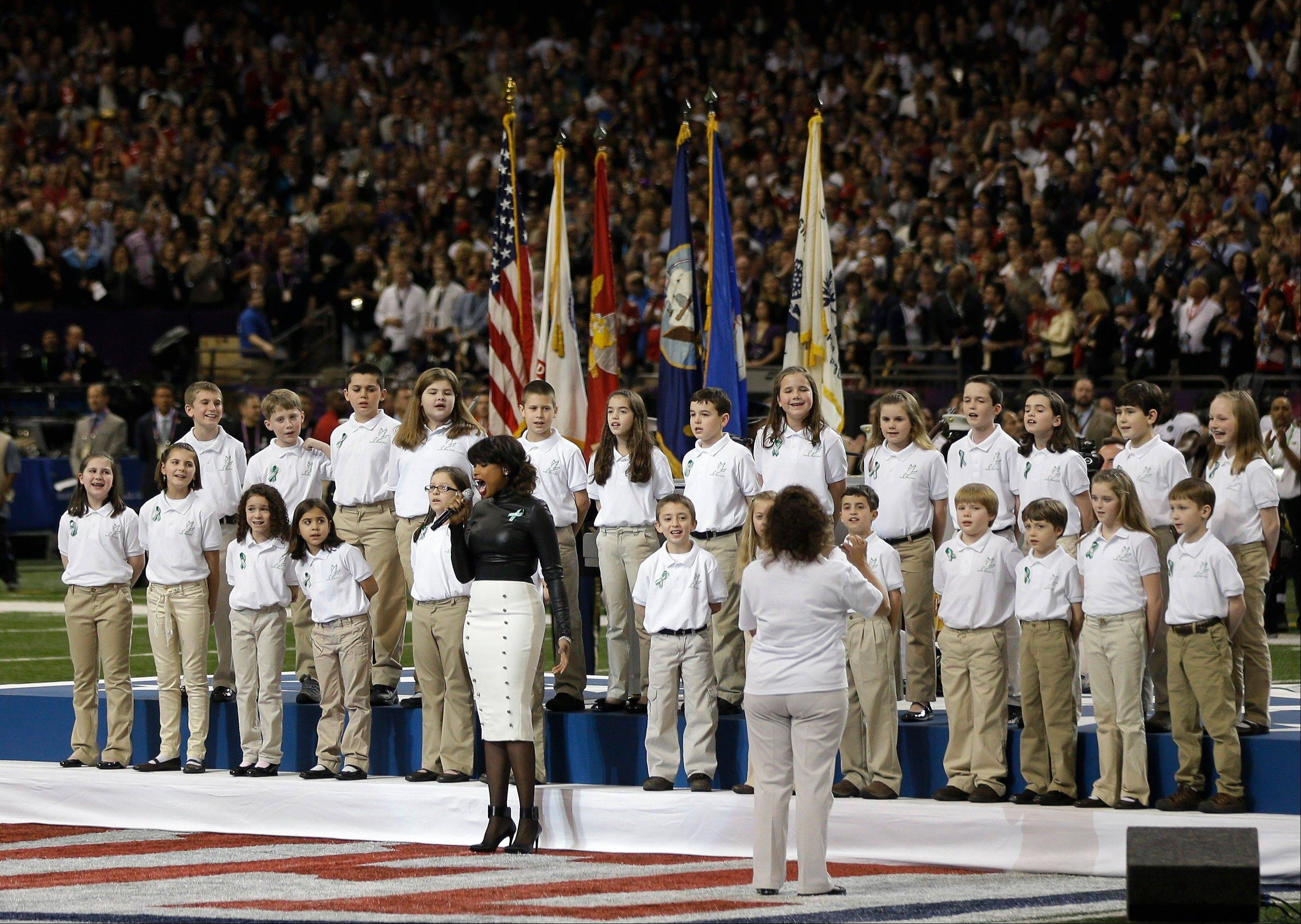 "Accompanied by students from Sandy Hook Elementary School, Jennifer Hudson, center, sings ""God Bless America"" before the Super Bowl on Sunday in New Orleans."