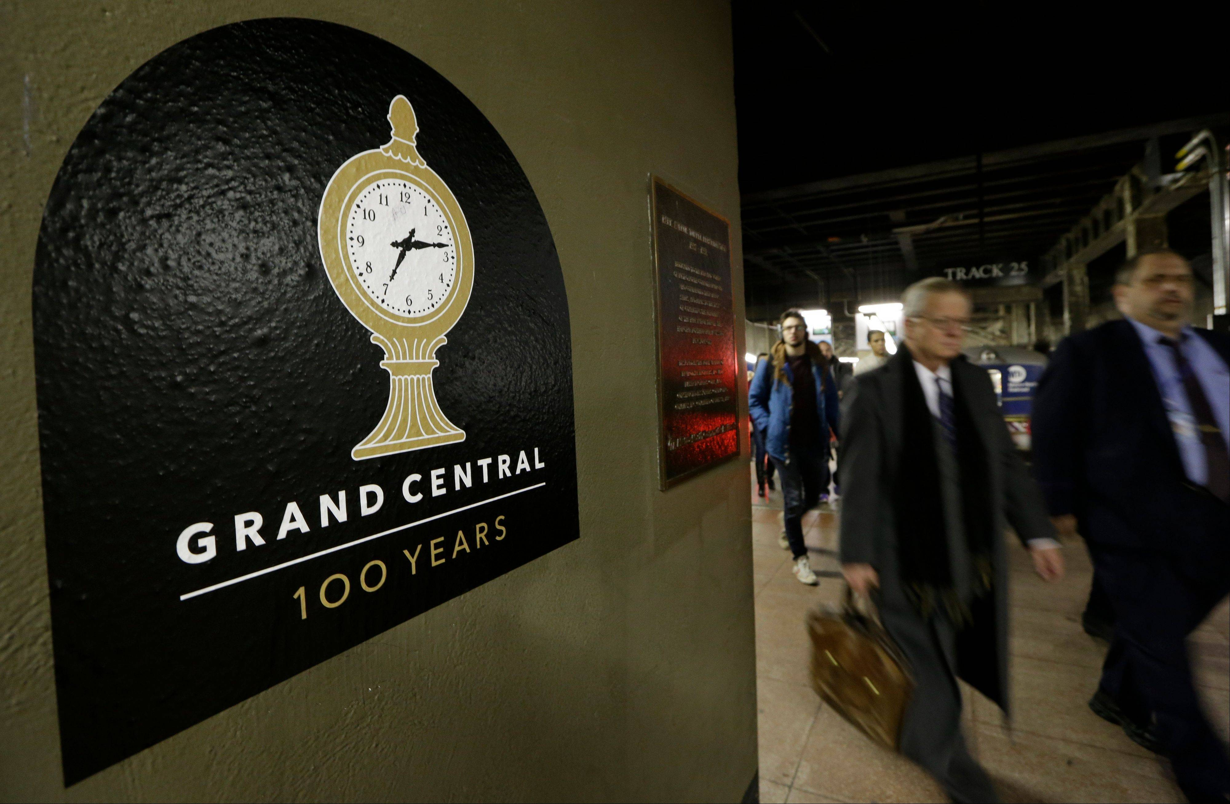Passengers disembark from a train past a sign advertising the 100th anniversary of Grand Central Terminal in New York. The country's most famous train station and one of the finest examples of Beaux Arts architecture in America turns 100 on Feb. 1.