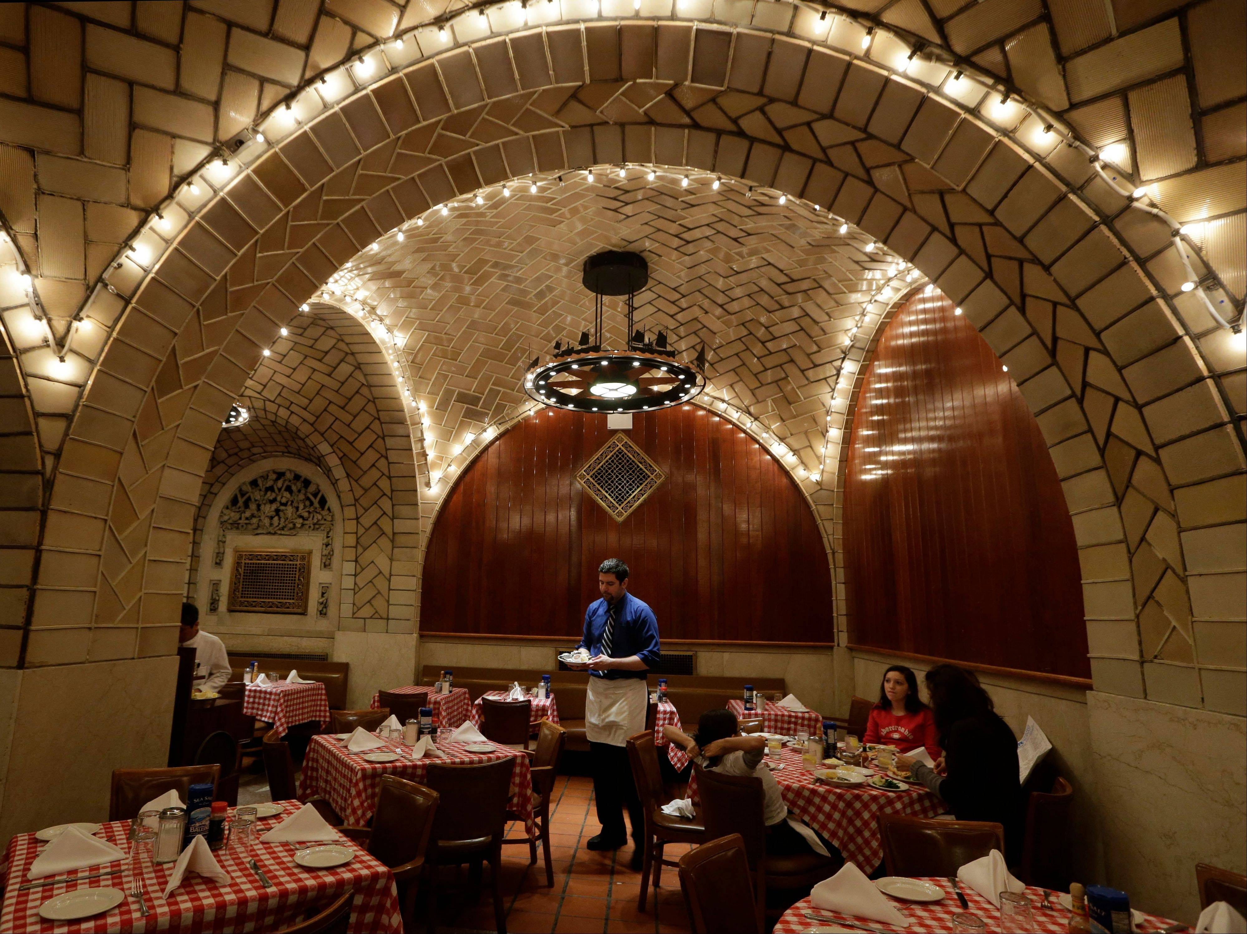 A server works beneath the tiled and vaulted ceilings at The Oyster Bar at Grand Central Terminal in New York.
