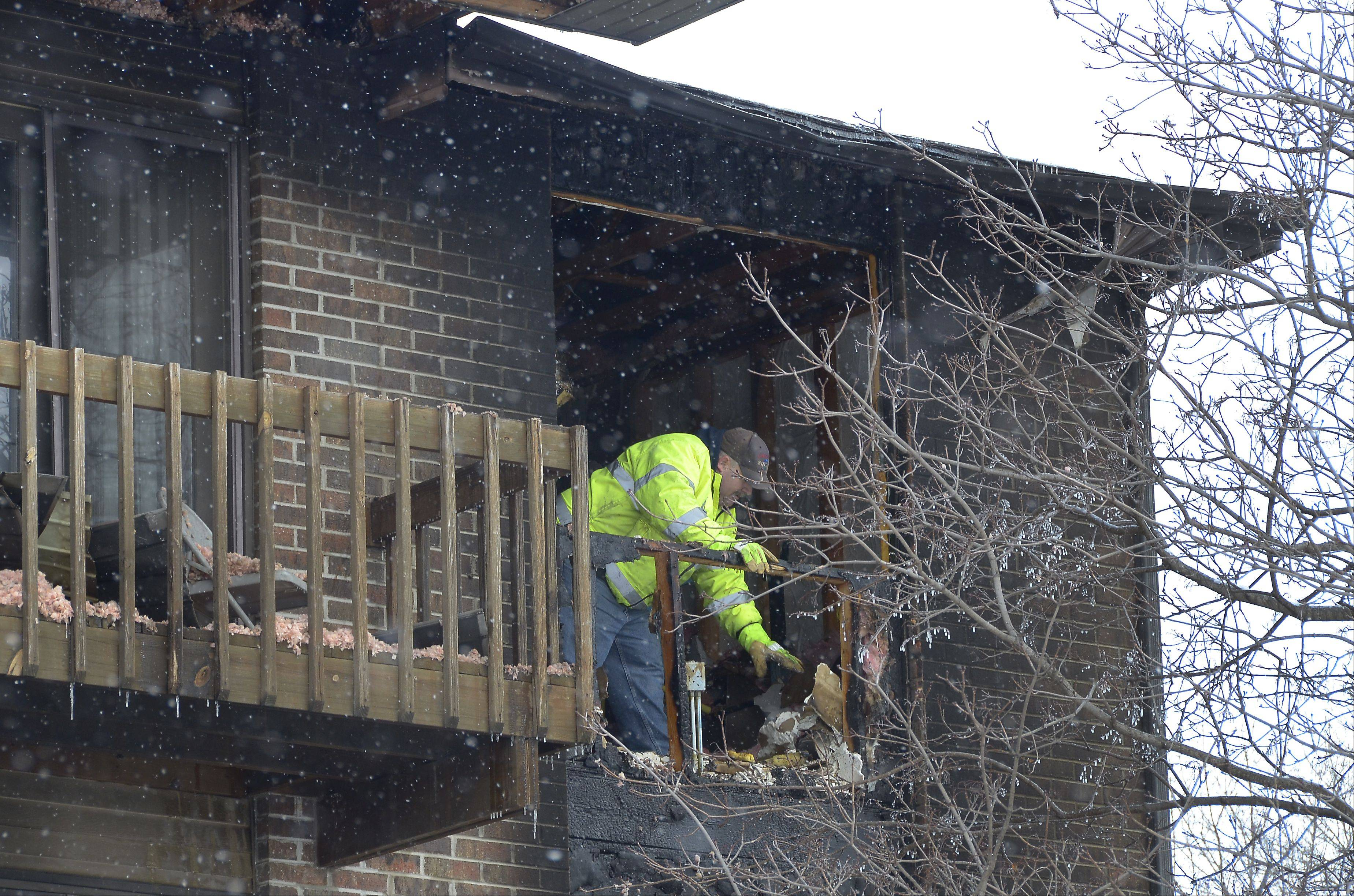 Tim Olk of 1-800 Board Up works at the scene of a fatal apartment fire Sunday morning in the Woodcreek Apartments complex in Huntley. Officials said one man was killed and about a dozen other residents were displaced by the early morning fire.