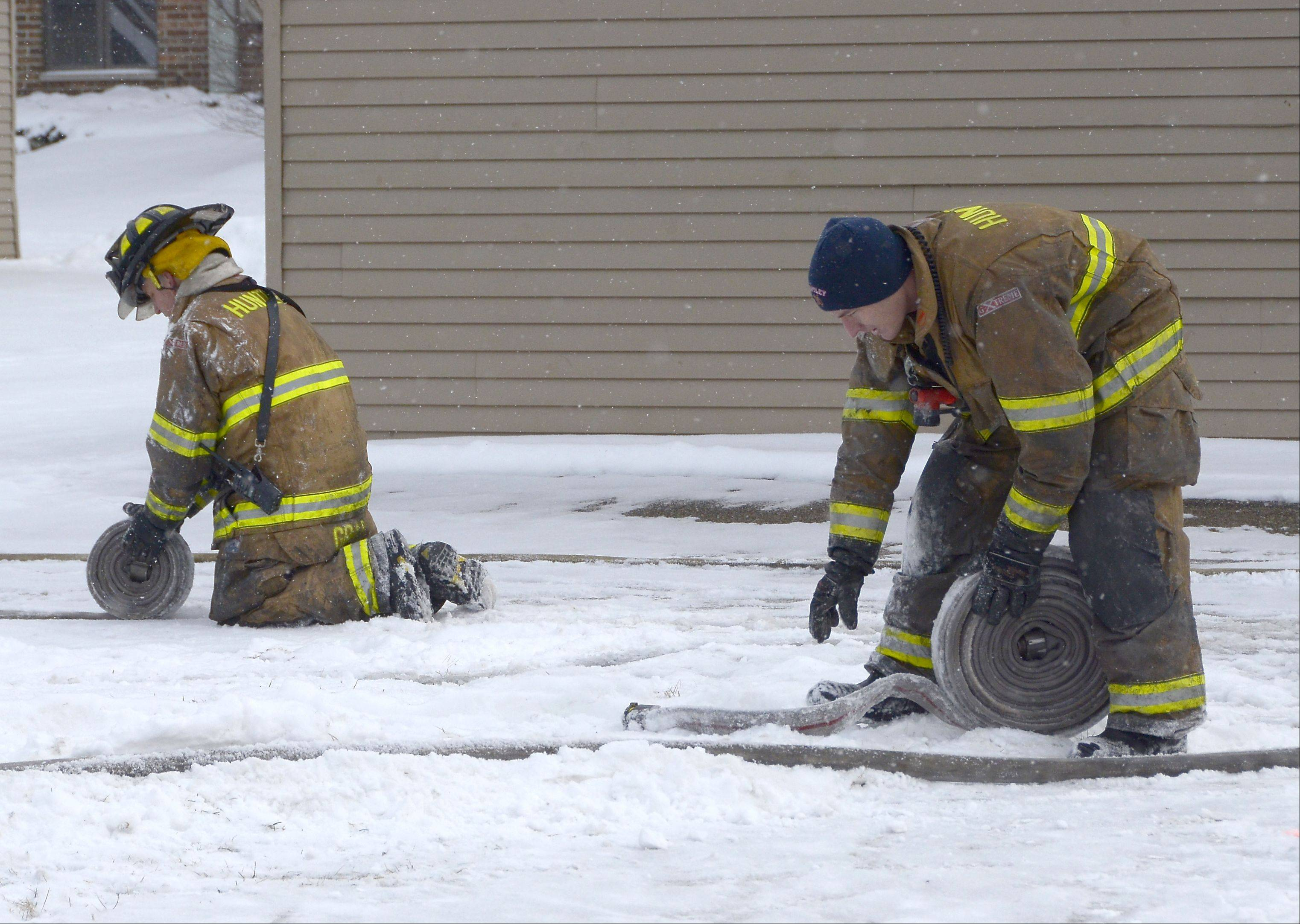 Firefighters roll up hoses at the scene of a fatal apartment fire Sunday morning in the Woodcreek Apartments complex in Huntley. Officials said one man was killed and about a dozen other residents were displaced by the early morning fire.