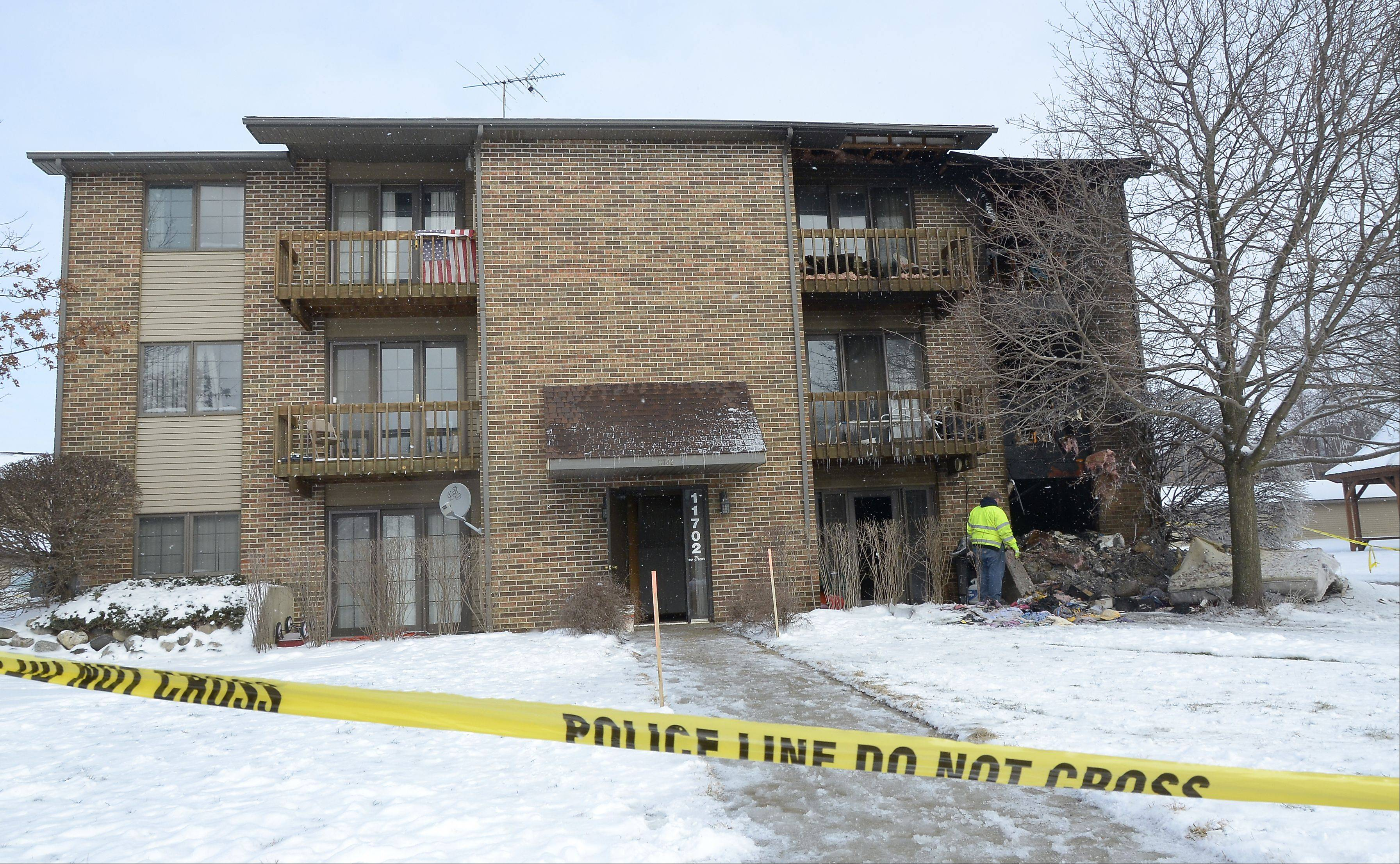 A firefighter works at the scene of a fatal apartment fire Sunday morning in the Woodcreek Apartments complex in Huntley. Officials said one man was killed and about a dozen other residents were displaced by the early morning fire.