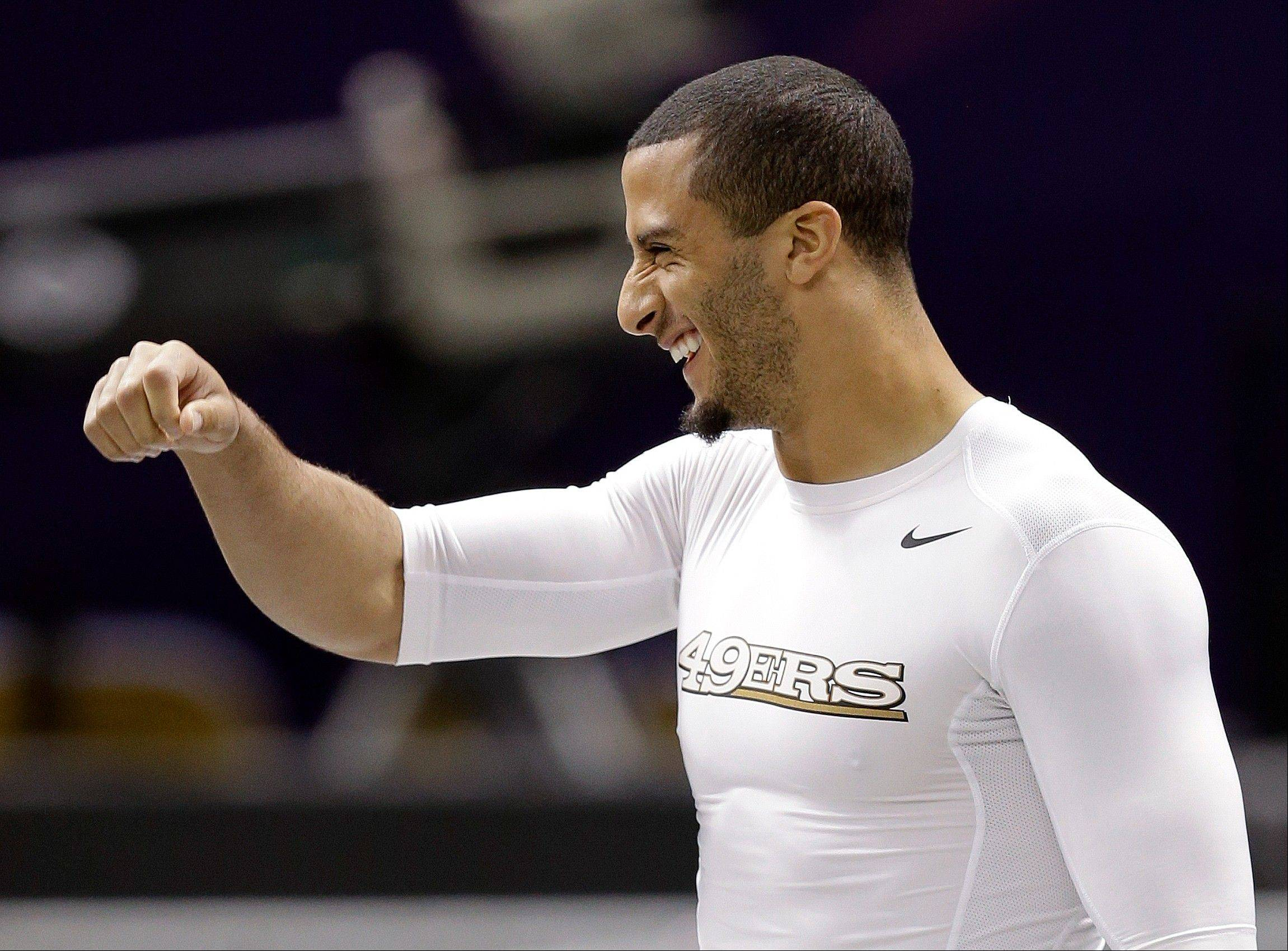 San Francisco 49ers quarterback Colin Kaepernick laughs as he walks onto the Superdome field for practice on Saturday.