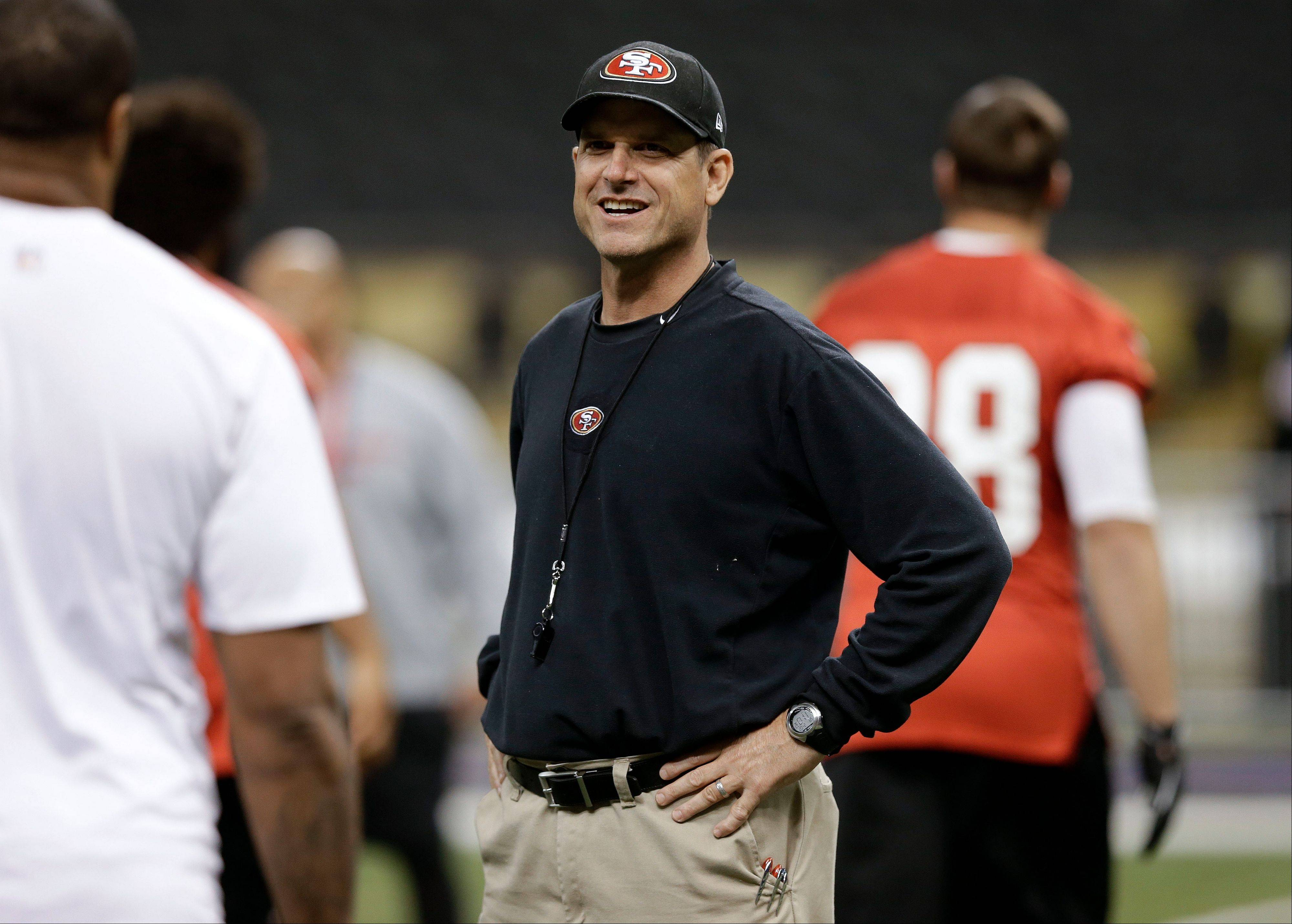 San Francisco 49ers head coach Jim Harbaugh talks with players during practice in the Superdome on Saturday.
