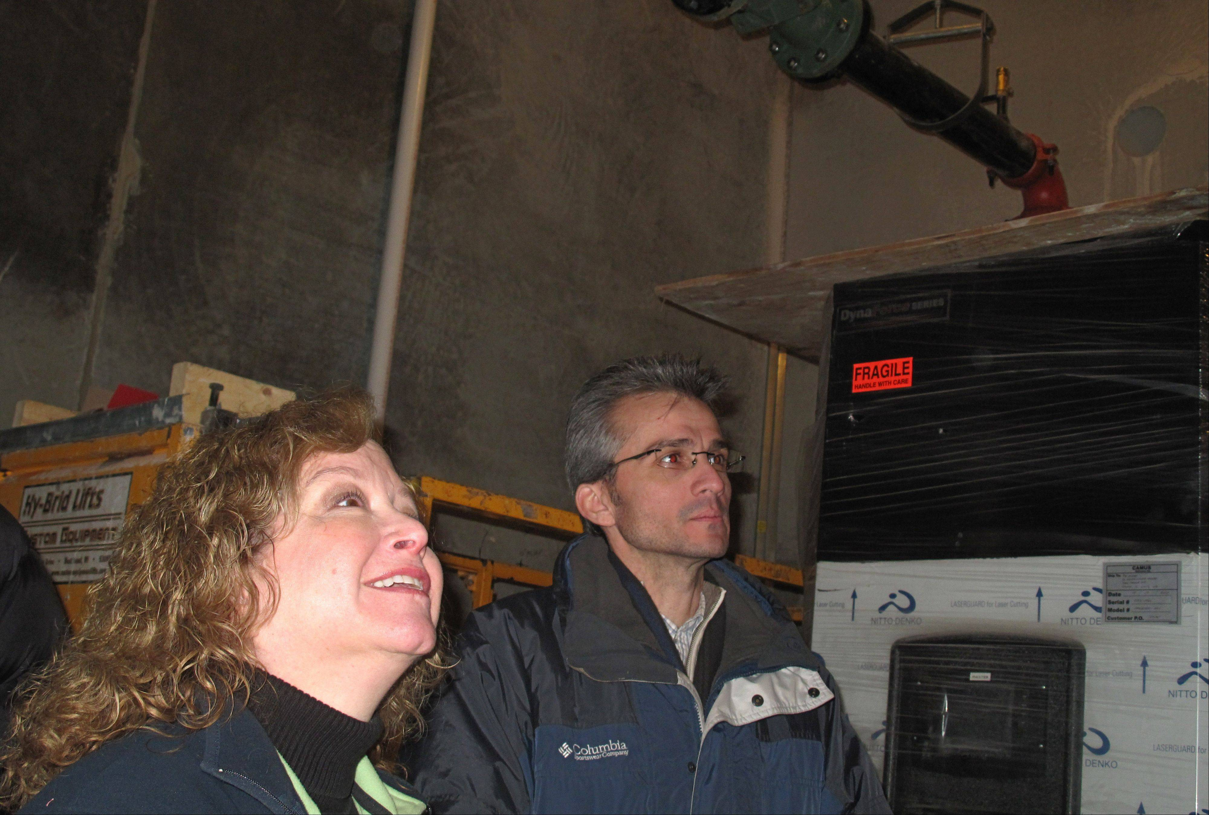 Carol Stream park board President Brenda Gramann and architect Frank Parisi examine the geothermal heating and cooling system Saturday at the Fountain View Recreation Center during a walk-through for parks officials. The system uses pumps to pull up underground air to assist in warming or cooling the building.