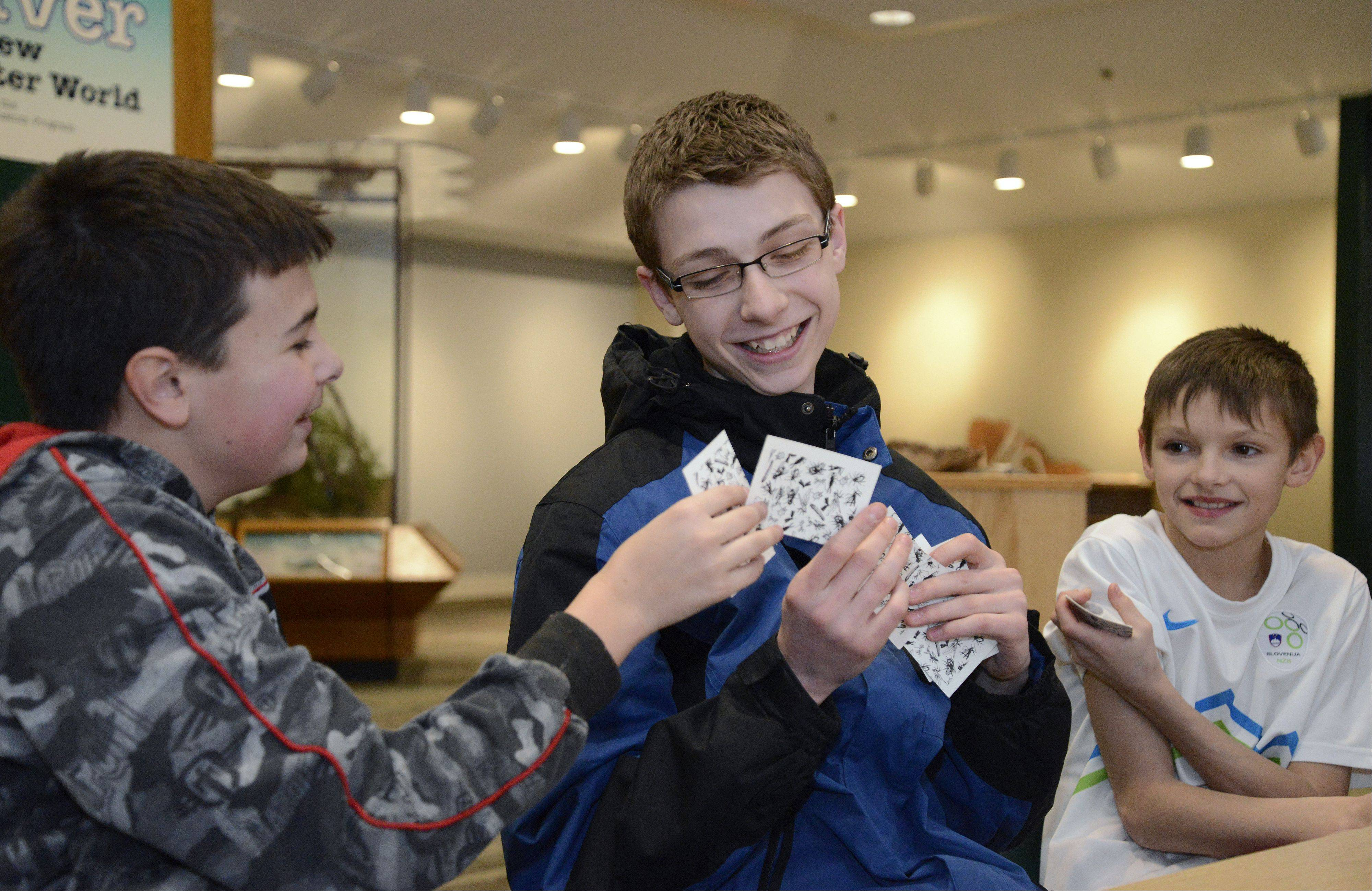 "From left, Trace Klehm, 13, of Barrington, and Thomas Grant, 13, of East Dundee play a nature version of ""go-fish"" with Jacob Zupan, 11, of Addison at the Forest Preserve District of Kane County's new Creek Bend Nature Center in St. Charles. Sixth- and seventh-graders from Harvest Christian Academy spent a few hours each day of the past week learning at the center as part of a class elective."
