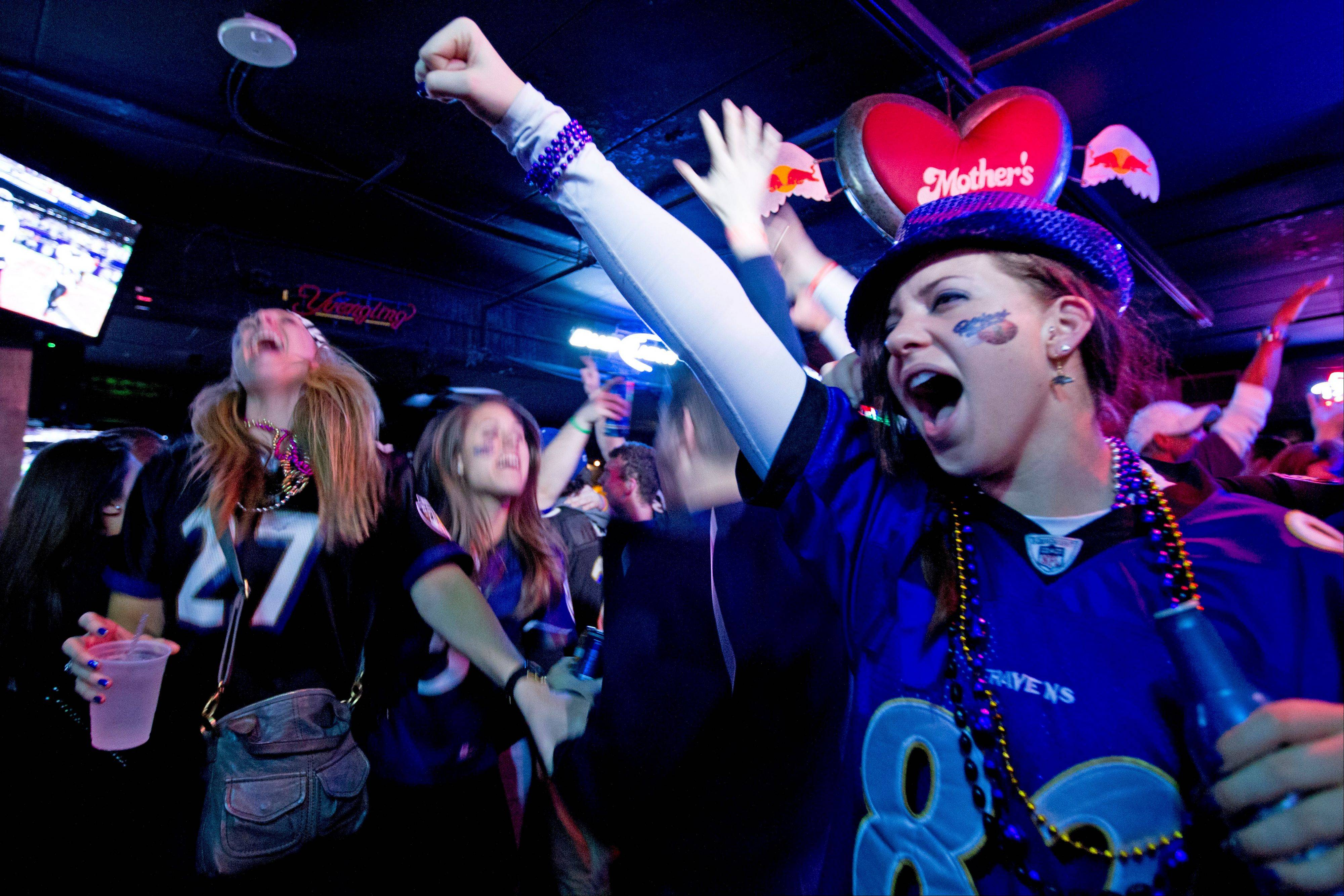 Ravens fans celebrate at a pub in Baltimore after their team scored the third touchdown against San Francisco 49ers on Sunday.