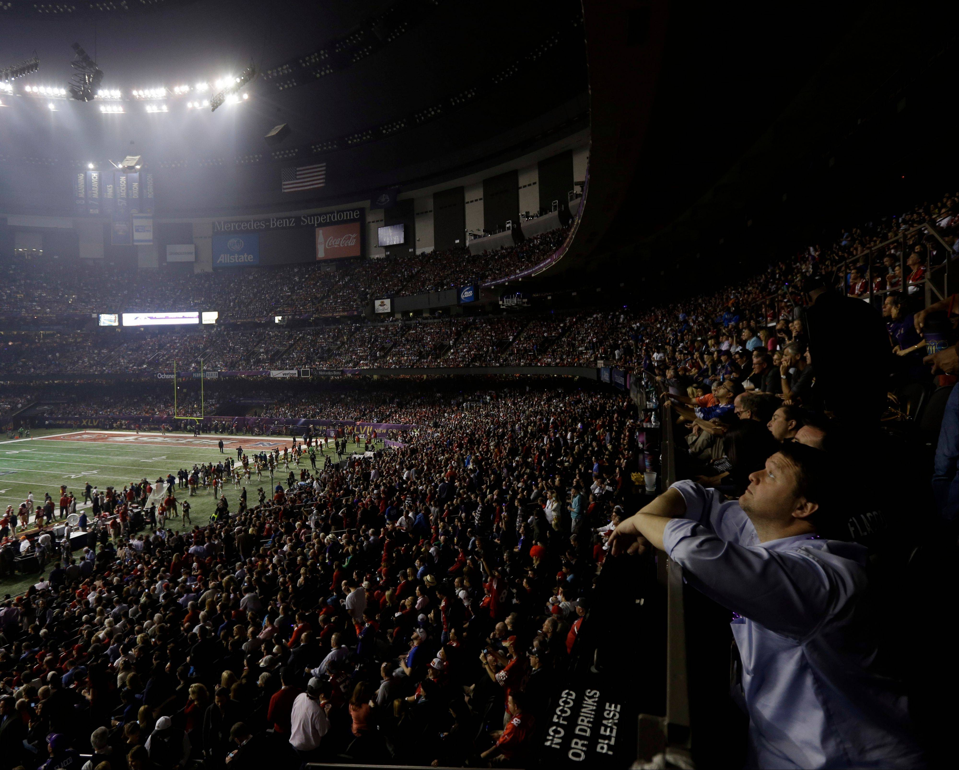 A fan looks around the Superdome after half the lights went out during a power outage in the second half of NFL Super Bowl XLVII on Sunday in New Orleans.