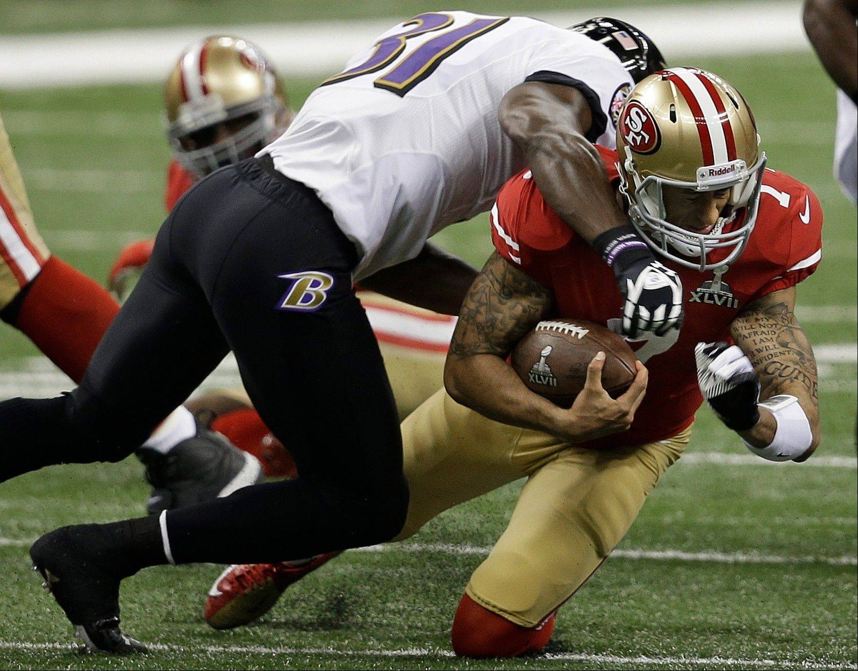 San Francisco 49ers quarterback Colin Kaepernick (7) is tackled by Baltimore Ravens safety Bernard Pollard (31) during the first half.