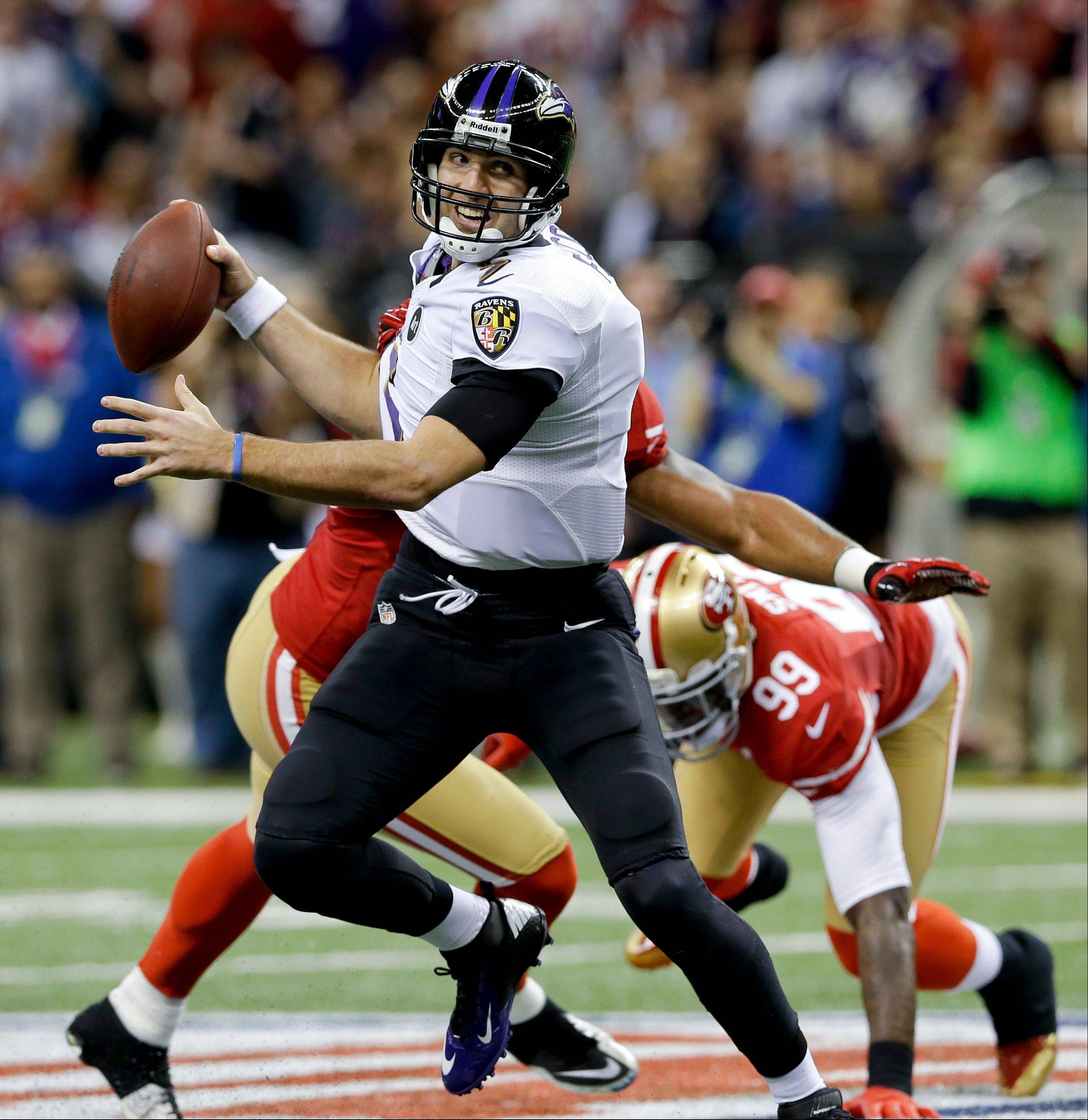 Baltimore Ravens quarterback Joe Flacco break away from San Francisco 49ers' Ahmad Brooks, left, and Aldon Smith (99) during the first half.