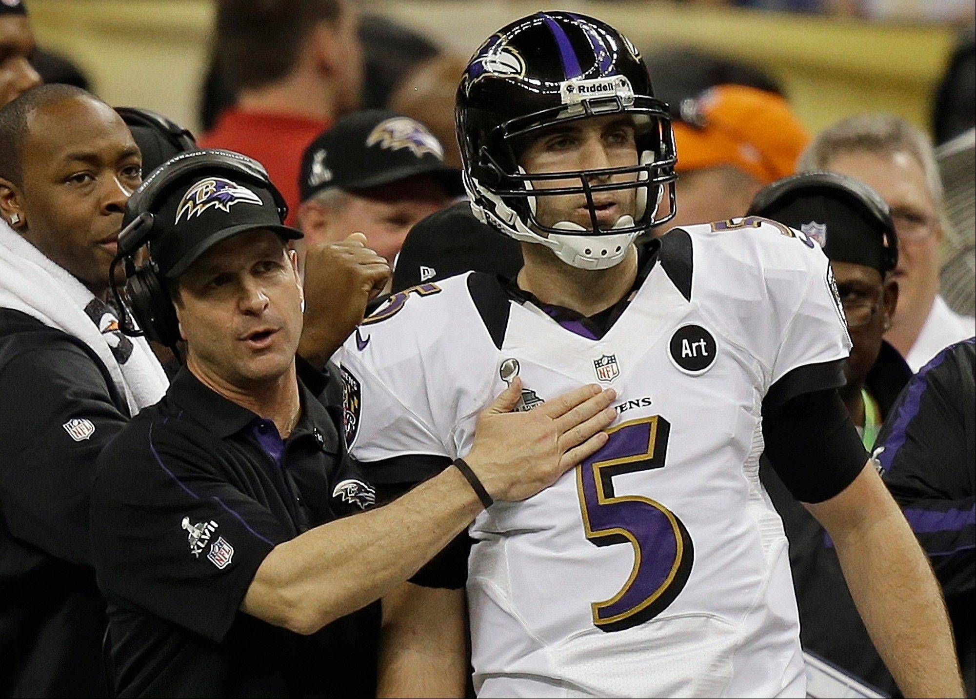 Baltimore Ravens head coach John Harbaugh talks with quarterback Joe Flacco (5) after the Ravens scored a touchdown against the San Francisco 49ers during the first half.