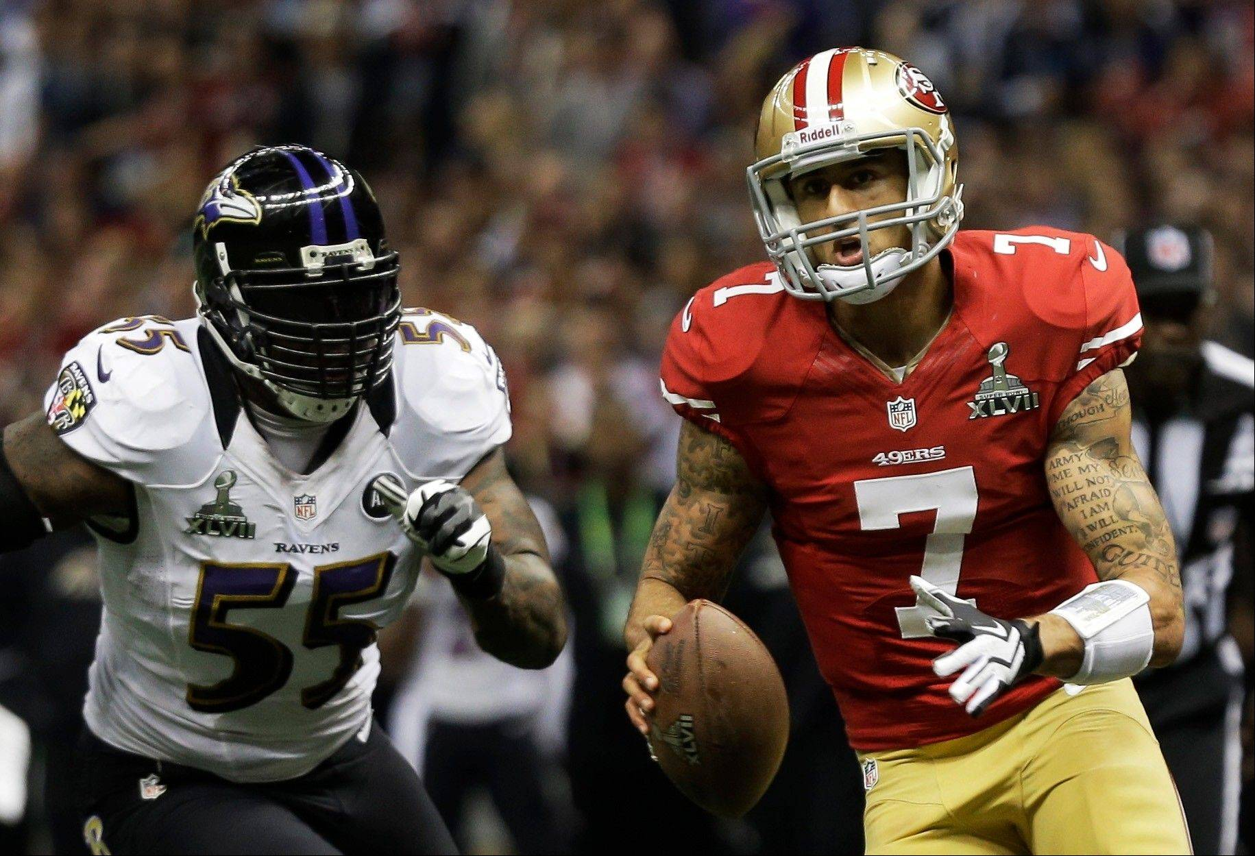 San Francisco 49ers quarterback Colin Kaepernick (7) carries the ball past Baltimore Ravens linebacker Terrell Suggs (55) during the first half.