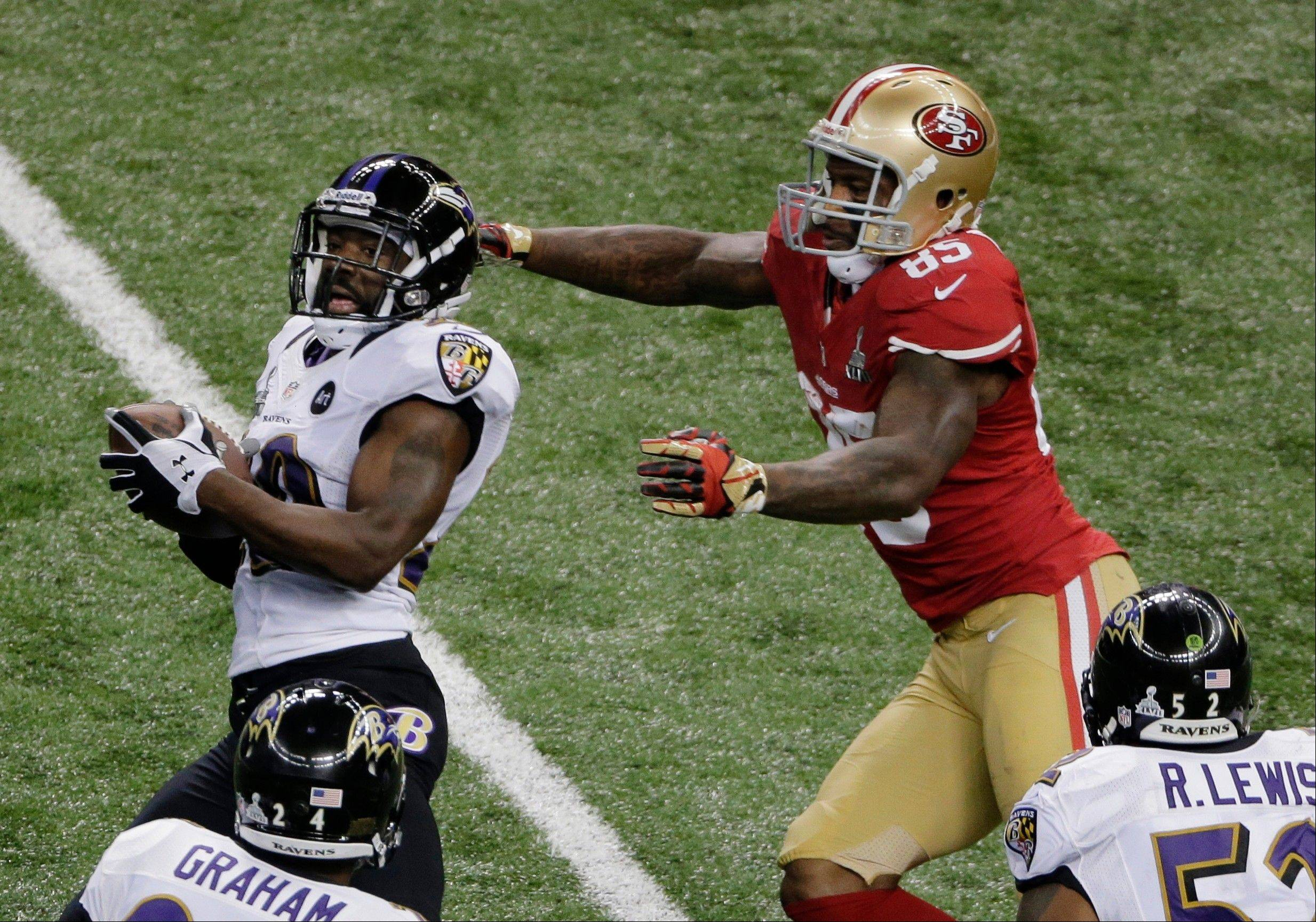 Baltimore Ravens safety Ed Reed (20) is tackled by San Francisco 49ers tight end Vernon Davis (85) after intercepting a pass during the first half.