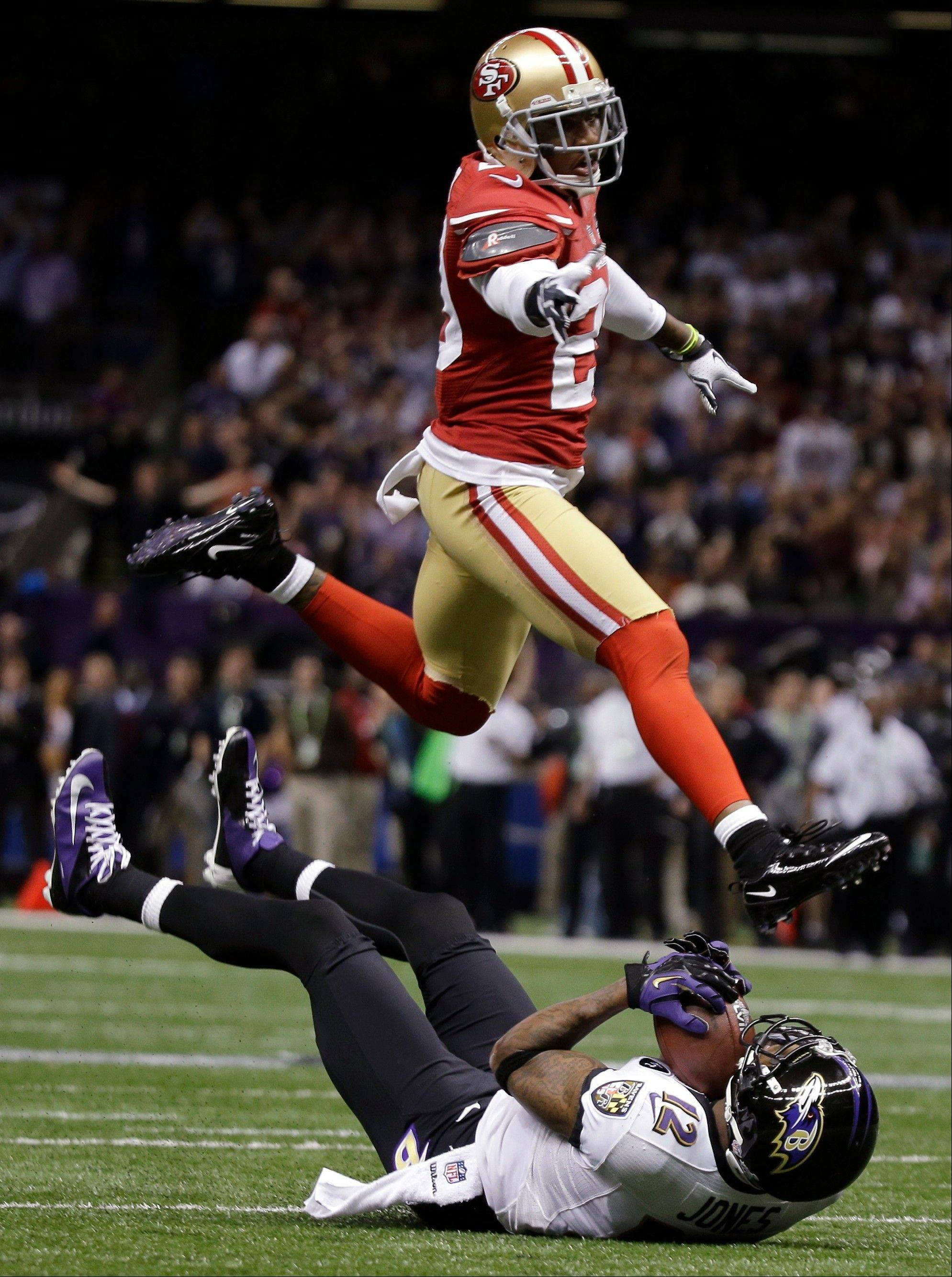 Baltimore Ravens wide receiver Jacoby Jones (12) catches the ball on the turf during a 56-yard touchdown reception in front of San Francisco 49ers defensive back Chris Culliver (29) in the first half.
