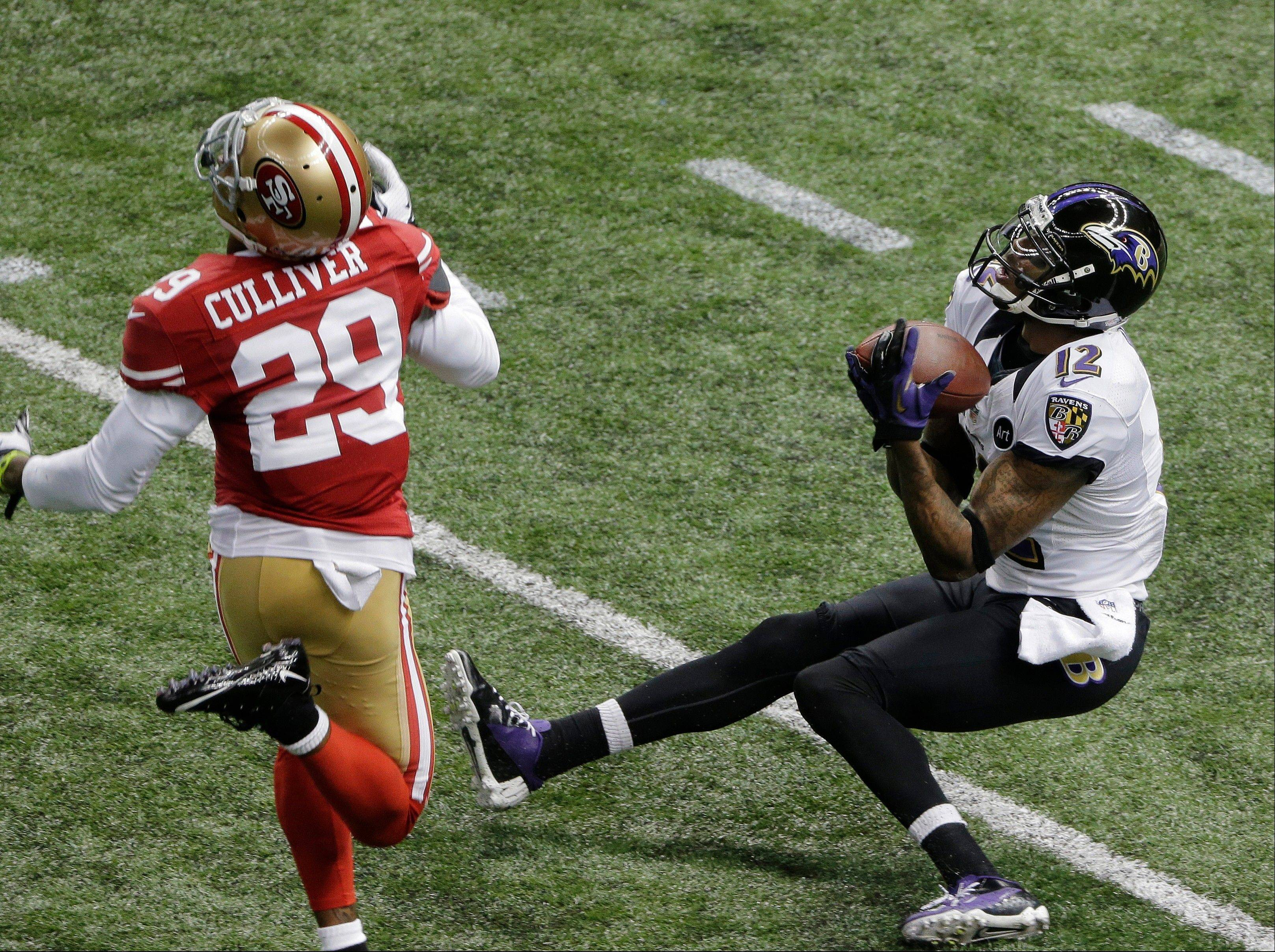 Baltimore Ravens wide receiver Jacoby Jones (12) catches a pass in front of San Francisco 49ers defensive back Chris Culliver (29) during the first half.