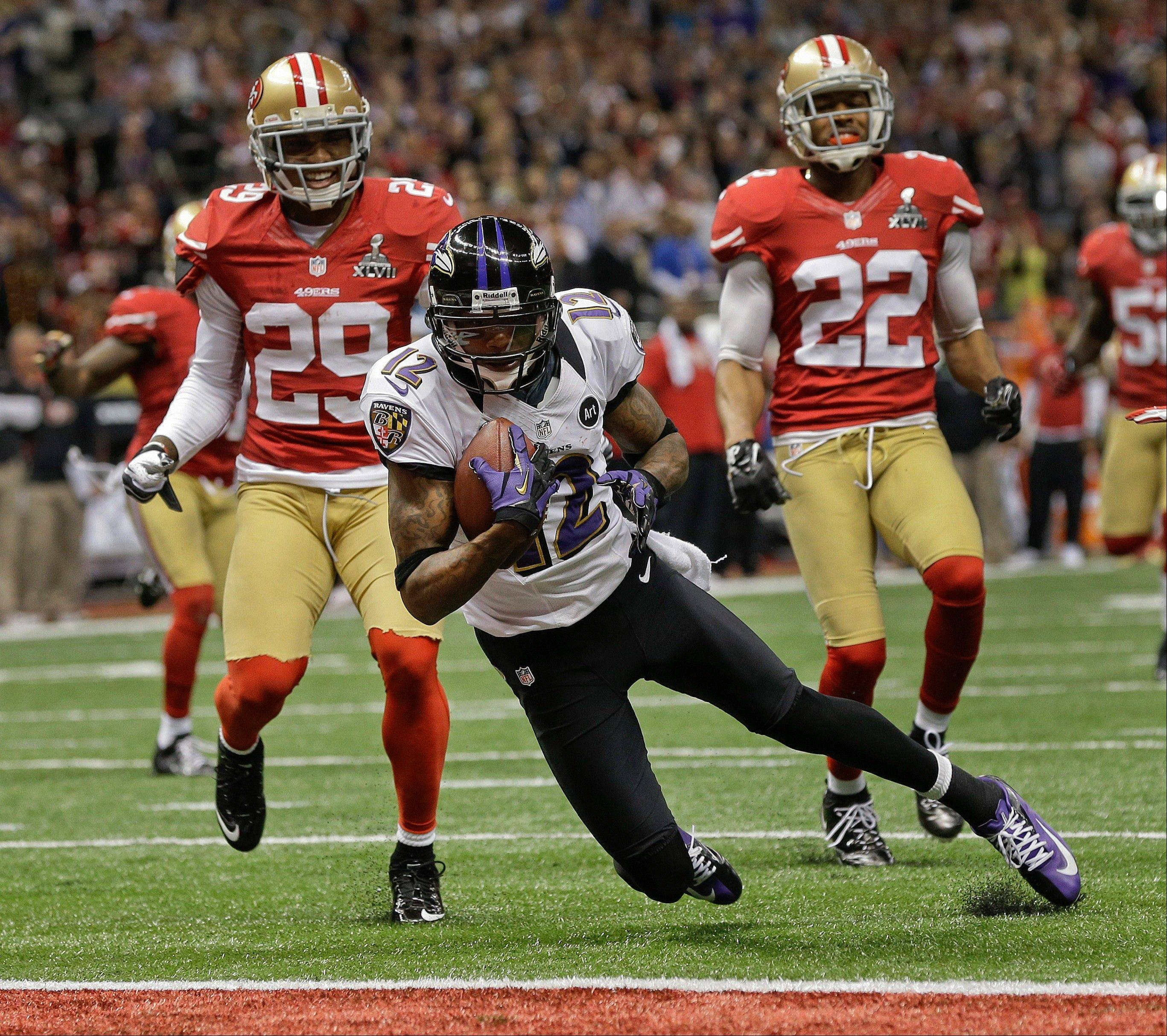 Baltimore Ravens wide receiver Jacoby Jones (12) crosses the goal line to score a 56-yard touchdown against San Francisco 49ers defensive back Chris Culliver (29) and cornerback Carlos Rogers (22) in the second quarter.