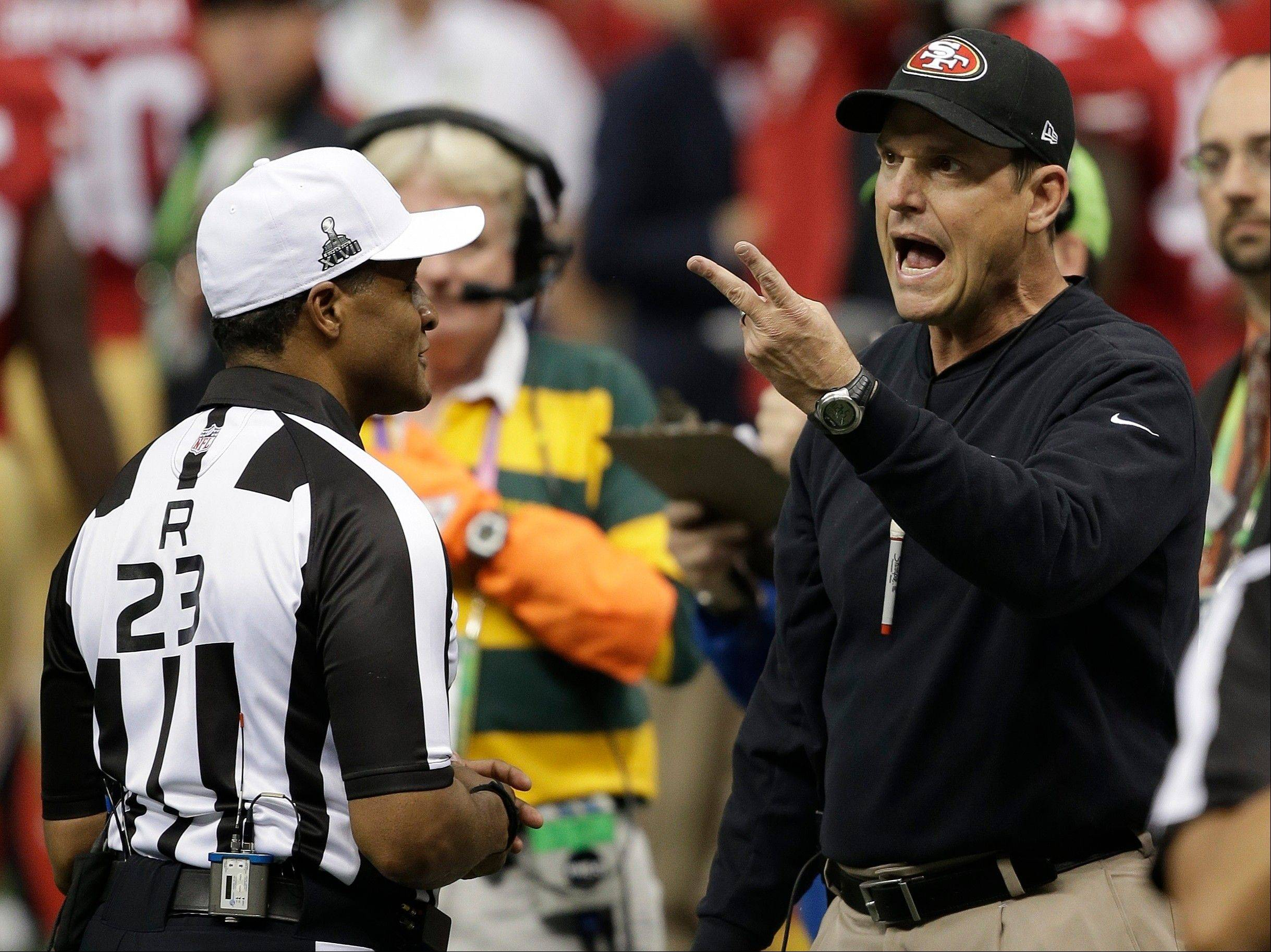 San Francisco 49ers head coach Jim Harbaugh, right, argues with referee Jerome Boger during the first half.