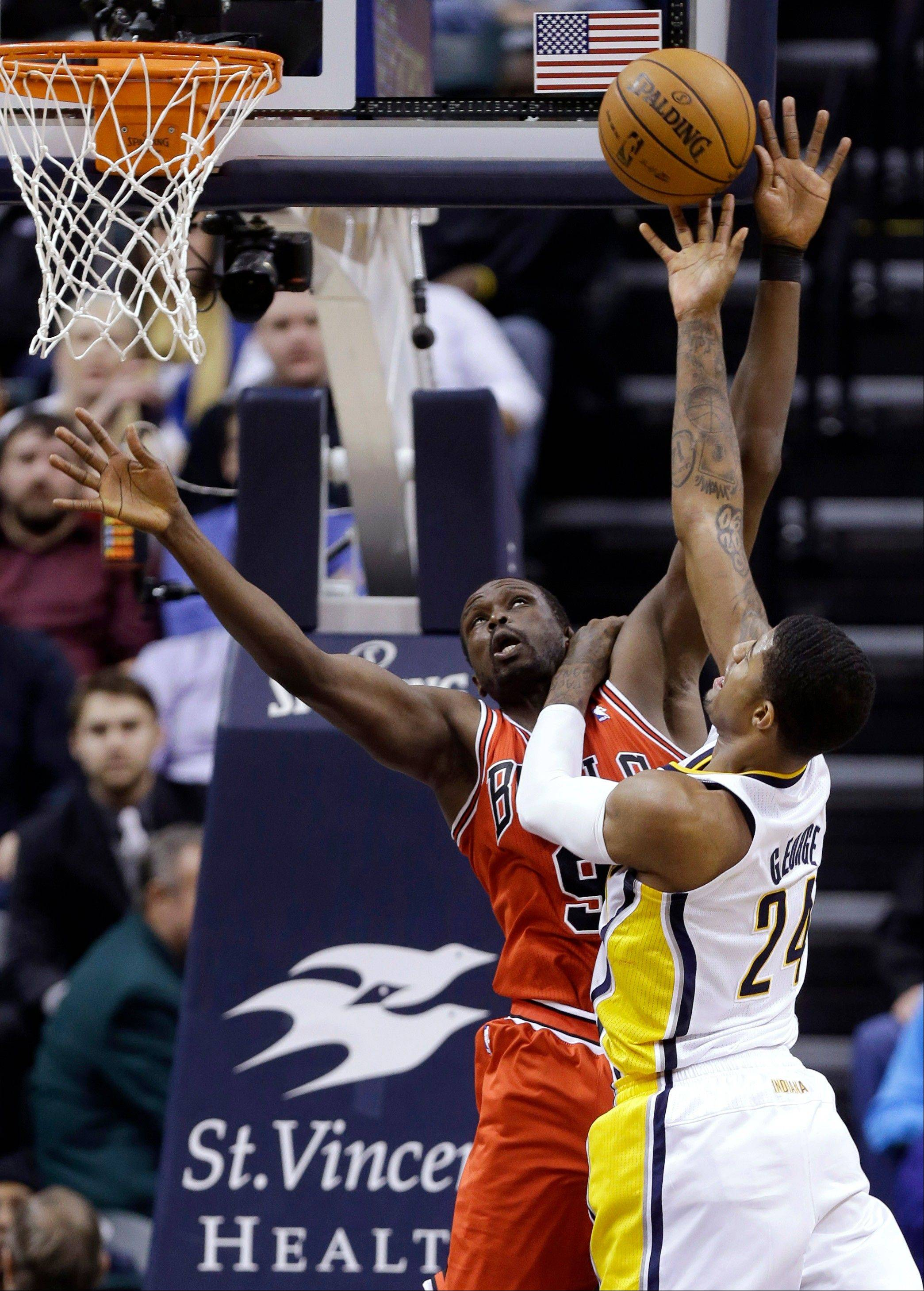 Pacers forward Paul George holds down Bulls forward Luol Deng as he shoots in the first half Monday night.