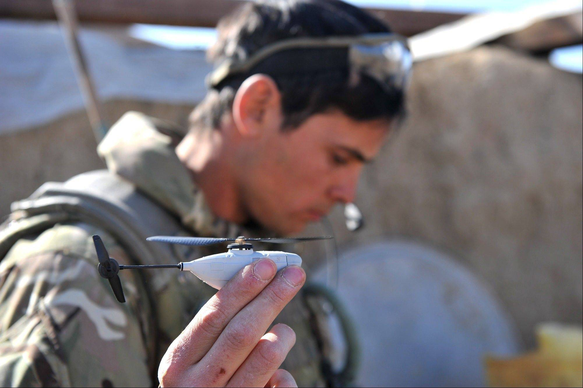 Sergeant Scott Weaver, of The Queens Royal Lancers launching a newly issued Black Hornet miniature surveillance helicopter during an operation in Afghanistan.