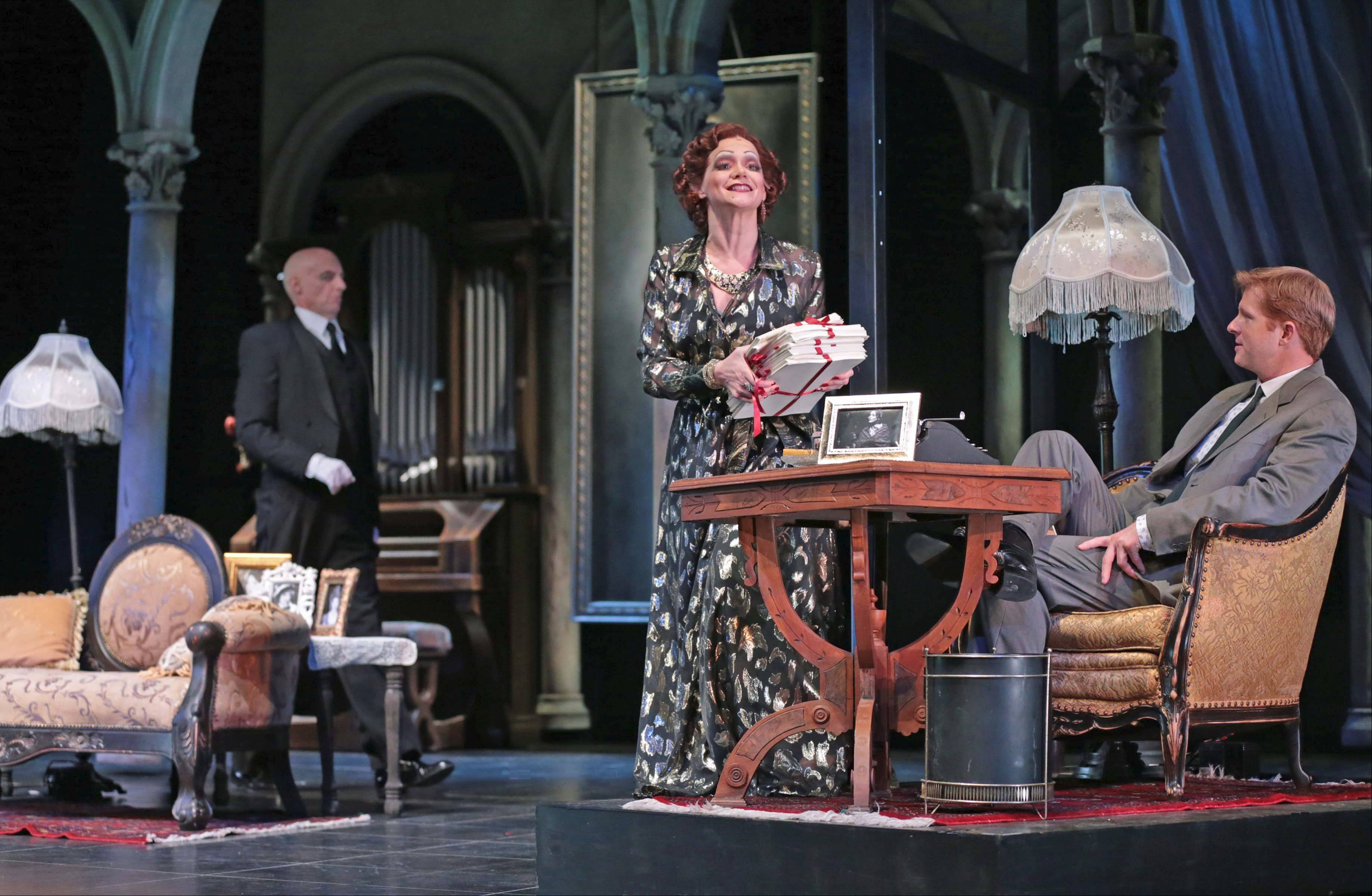 "Faded movie star Norma Desmond (Christine Sherrill) invites screenwriter Joe Gillis (Will Ray, right) to examine her comeback screenplay of ""Salome"" while butler Max (Don Richard, left) looks on in ""Sunset Boulevard"" at Drury Lane Theatre in Oakbrook Terrace."