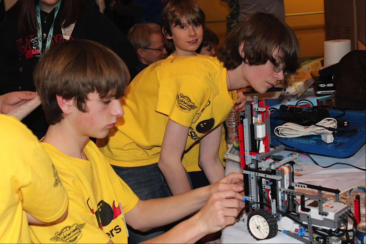 Jasper Pasternak and Josh Beedy make adjustments to the robot in the team's pit prior to heading to a competition run at the First Lego League state tournament last month at Forest View Educational Center in Arlington Heights.