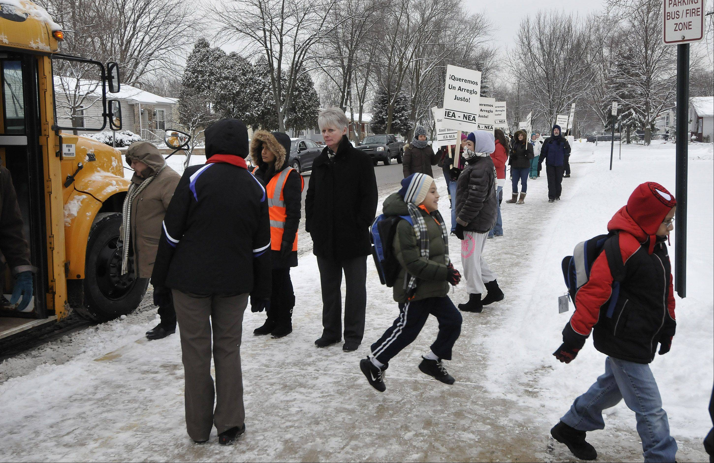 Students are escorted into Pioneer Elementary School Monday to attend alternative programs while teachers in West Chicago Elementary District 33 remain on strike.