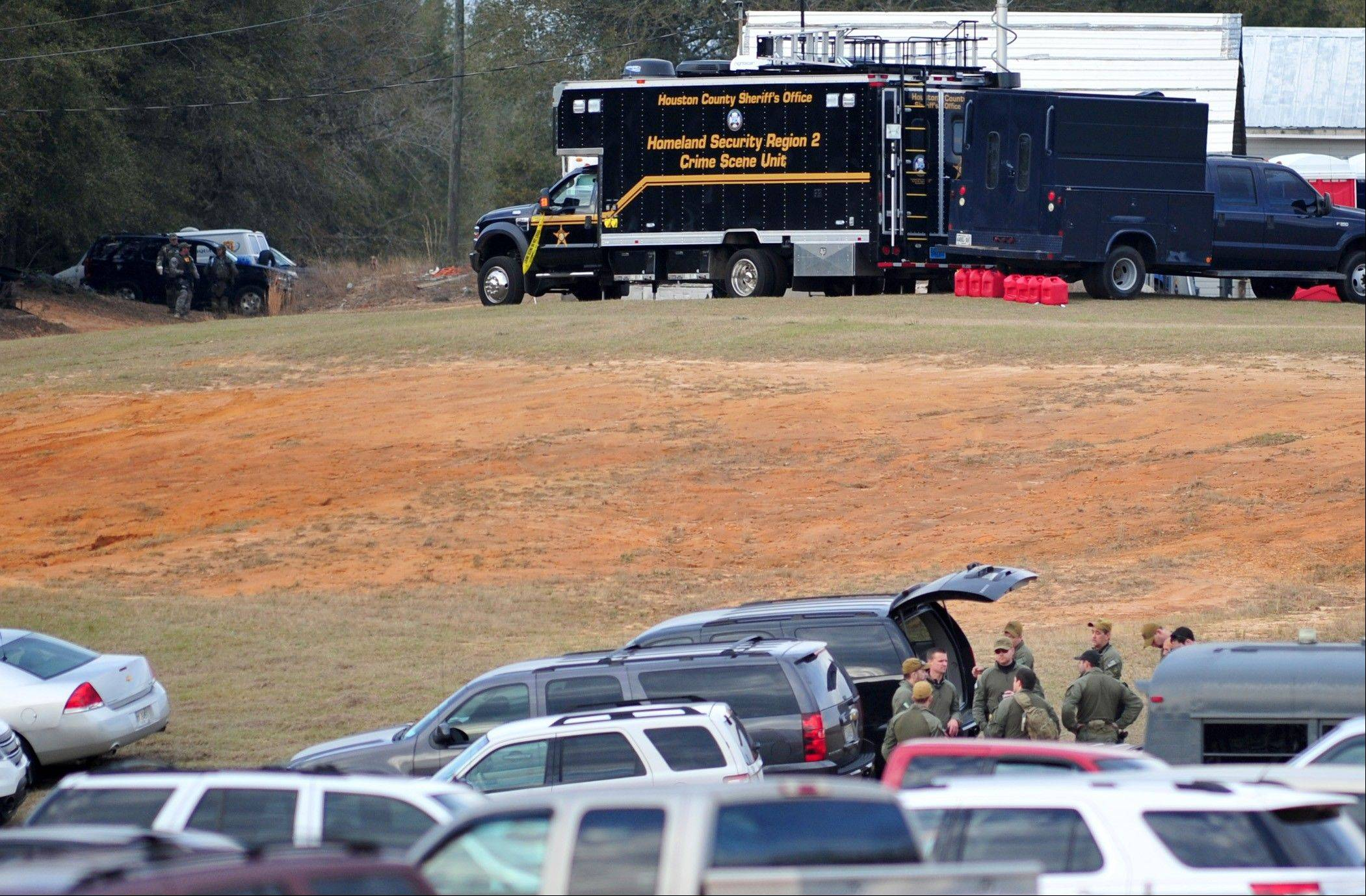 Federal and local law enforcement officers gather at their trucks after the hostage crisis ended in Midland City, Ala., Monday afternoon. Officials say they stormed a bunker in Alabama to rescue a 5-year-old child being held hostage there after his abductor was seen with a gun.