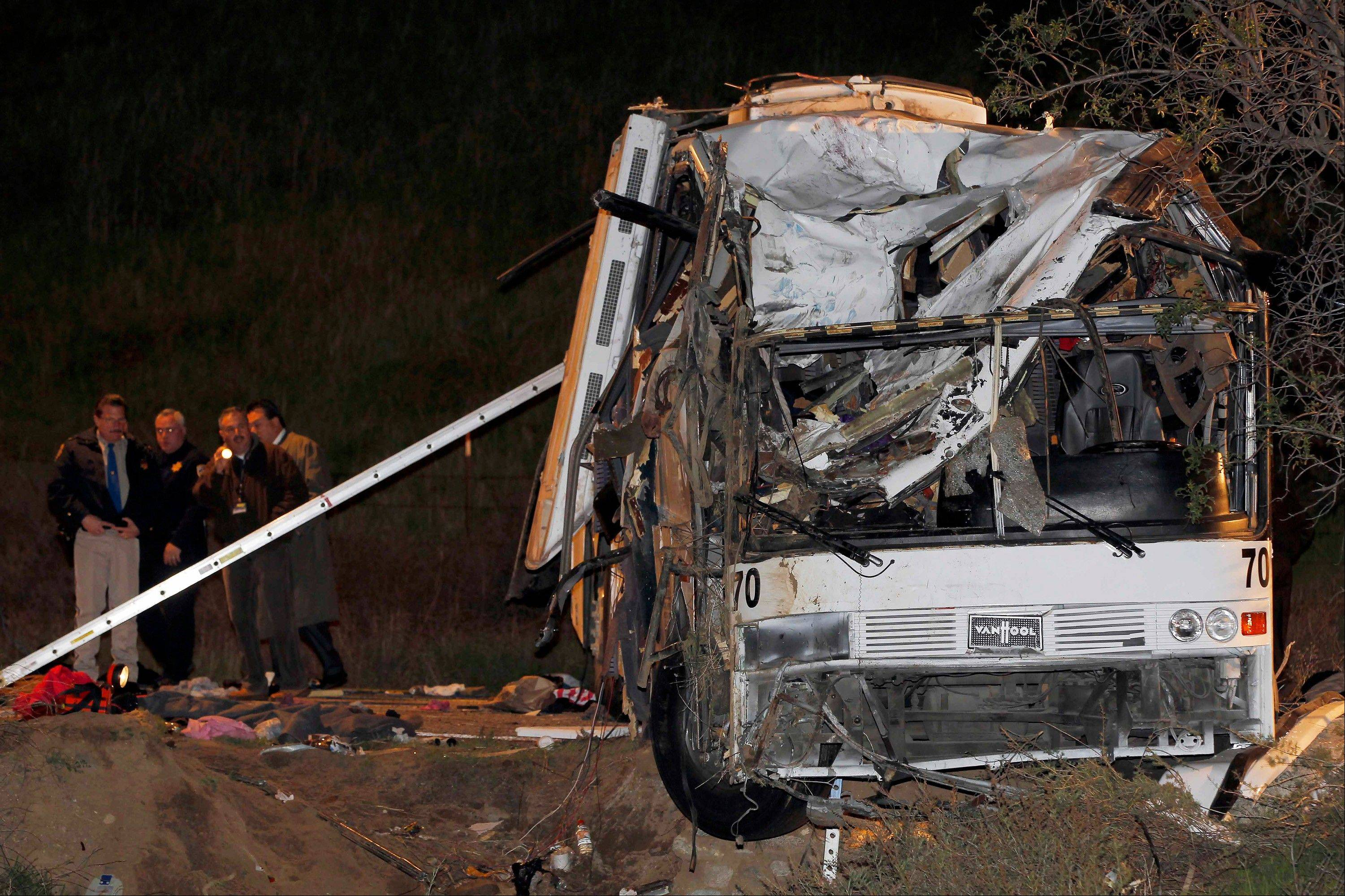 Investigators continue working the scene where at least eight people were killed and 38 people were injured after a tour bus carrying Mexican tourists careened out of control while traveling down a mountain road, struck a car, flipped and plowed into a pickup truck, near Yucaipa, Calif., Sunday.