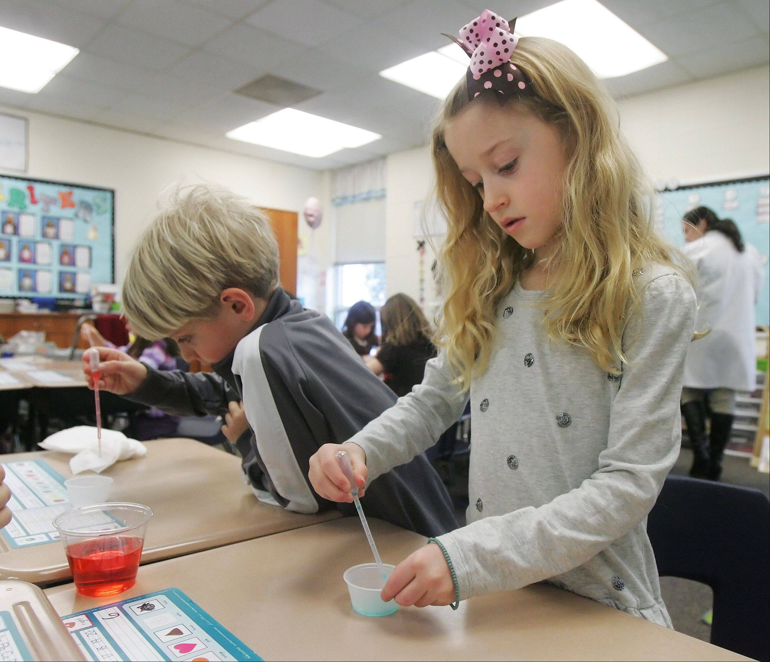 "First graders Brenna Hornsey, right, and Lucas Kallieris, work on an experiment during the ""What's The Matter"" program by High Touch High Tech Monday for first grade students at Butterfield School in Libertyville. The kids learned about changing physical properties with a hands-on experiment using crystals and colored water."