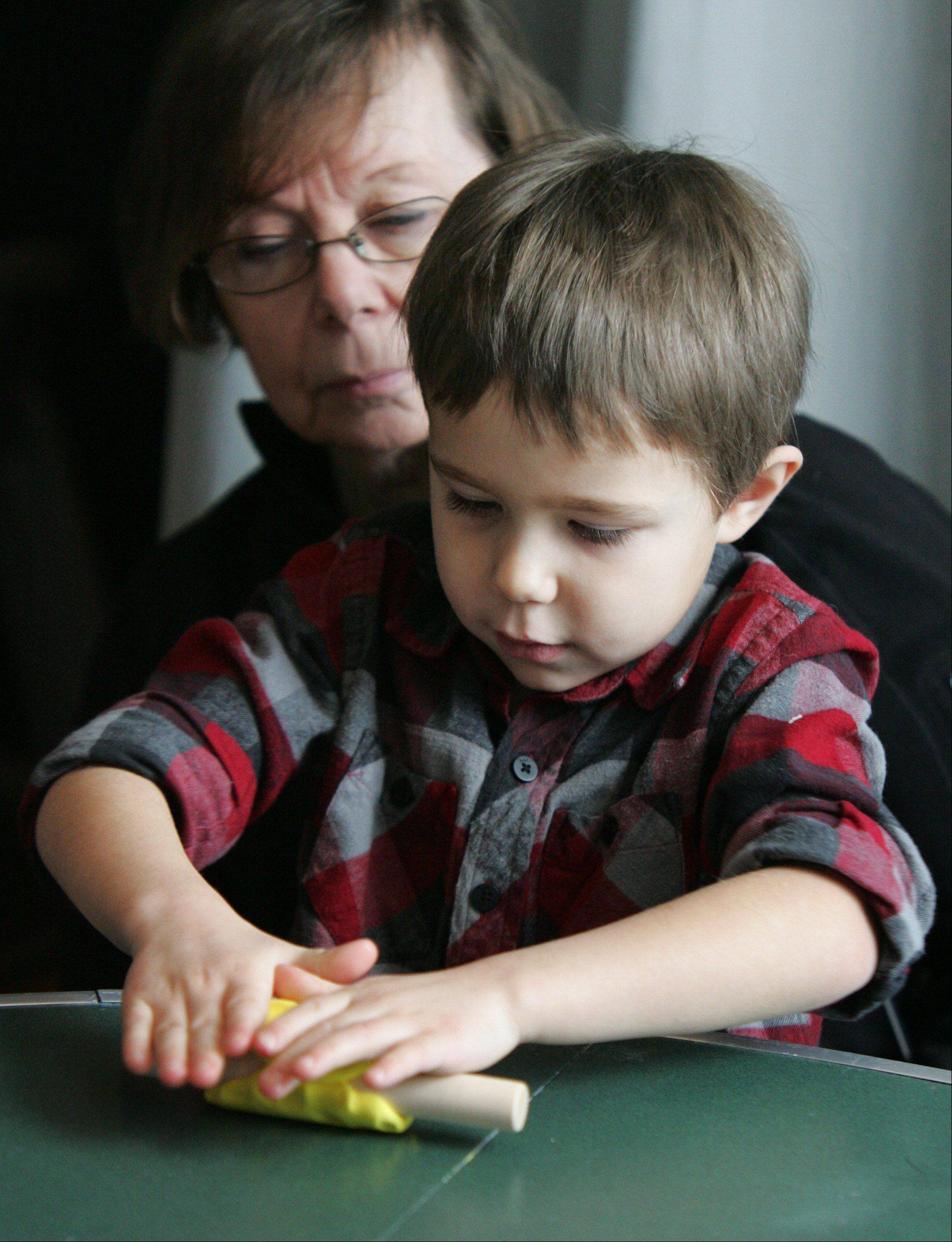 "Clay Scheck, 4, of Wauconda, rolls clay with help from his grandmother, Barbara Lane, during the ""Play With Clay; Small Discoveries"" program at the Lake County Discovery Museum in Lakewood Forest Preserve near Wauconda."