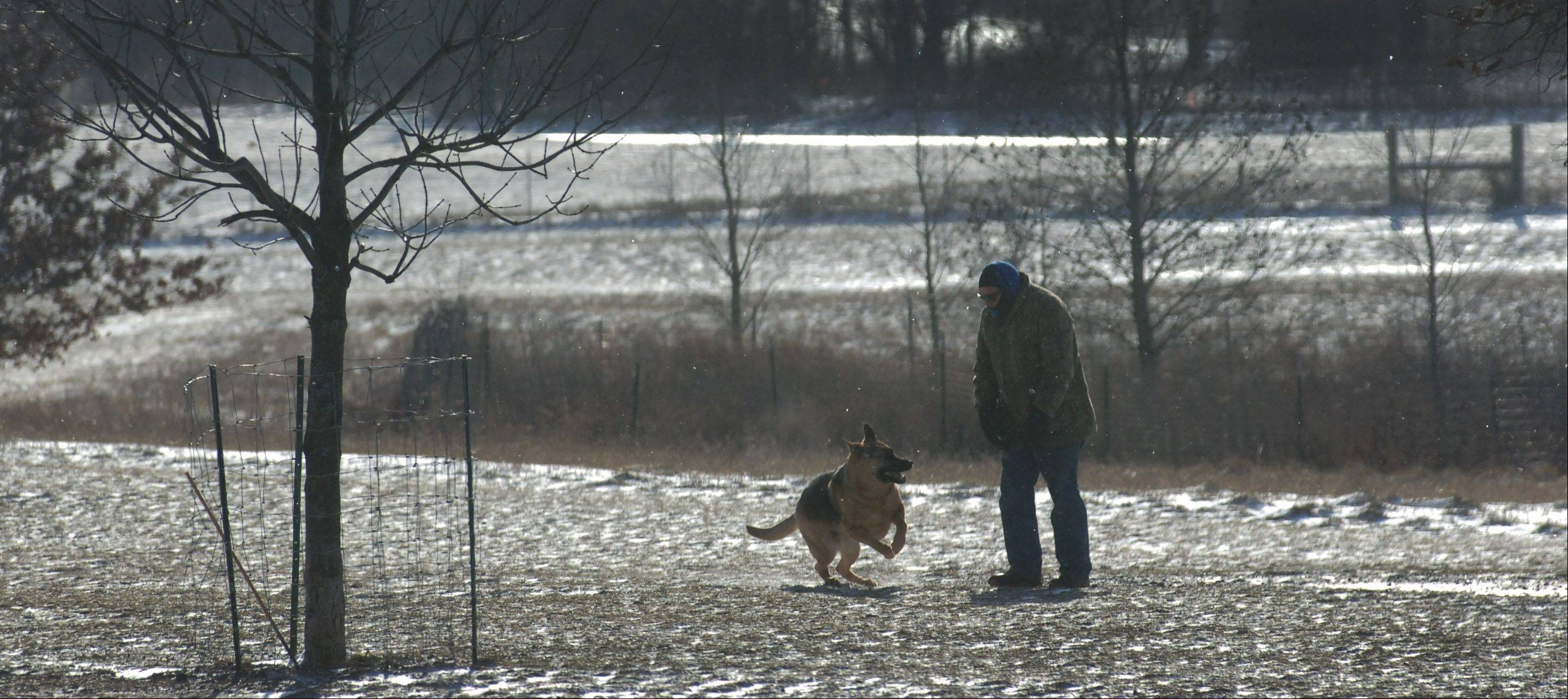 On Tuesday, visitors of the Lakewood Dog Exercise Area near Wauconda were enjoying temperatures in the 60's. Thursday's temperatures were radically different. Mundelein resident Tony Farina bundled up against the cold and visits with a German Shepherd who paid him a visit.