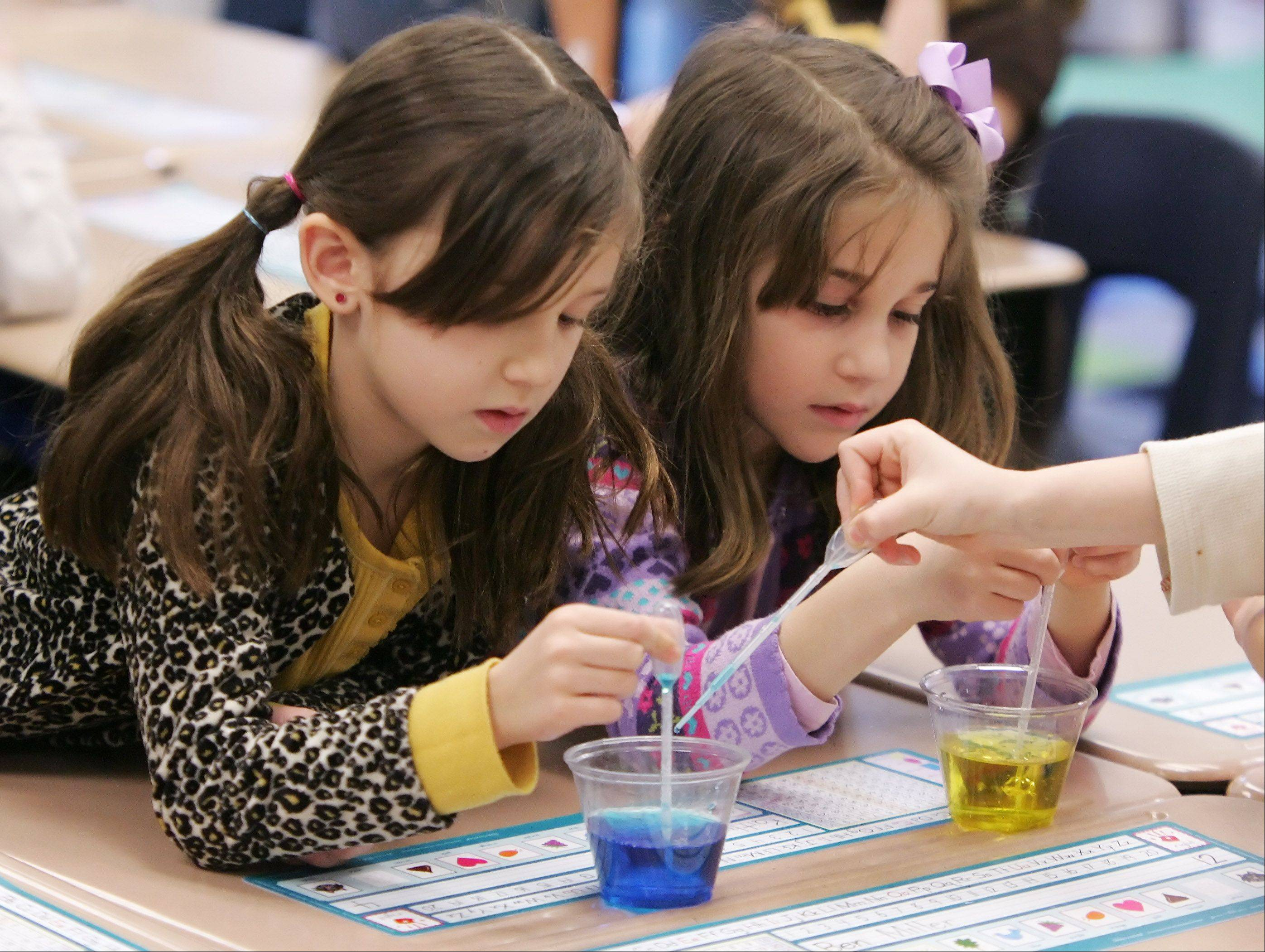 "Natalia Remter, left, and Katherine Caronis mix color into water during the ""What's The Matter"" program by High Touch High Tech Monday for first grade students at Butterfield School in Libertyville."