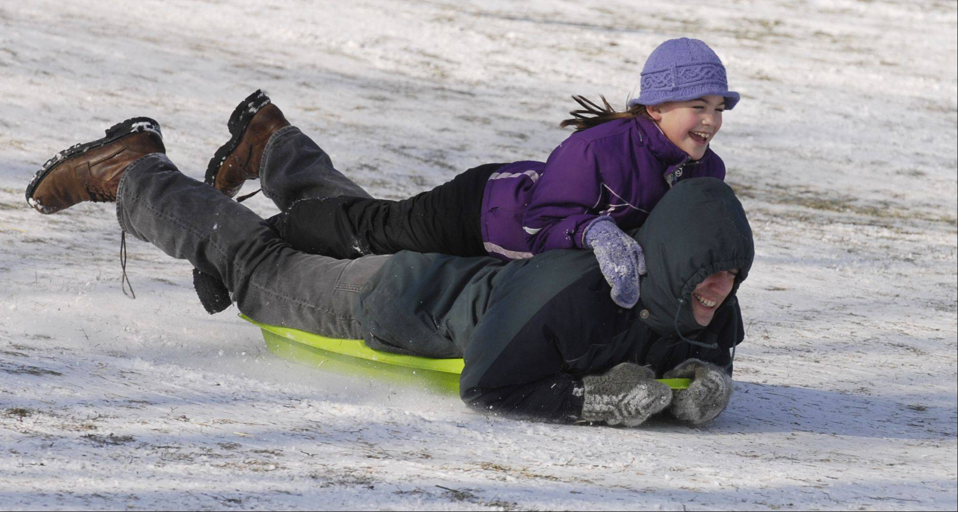 Doug Pekny and his daughter Noelle, 8, of Glen Ellyn, enjoy the day sledding at Newton Park in Glen Ellyn Sunday.