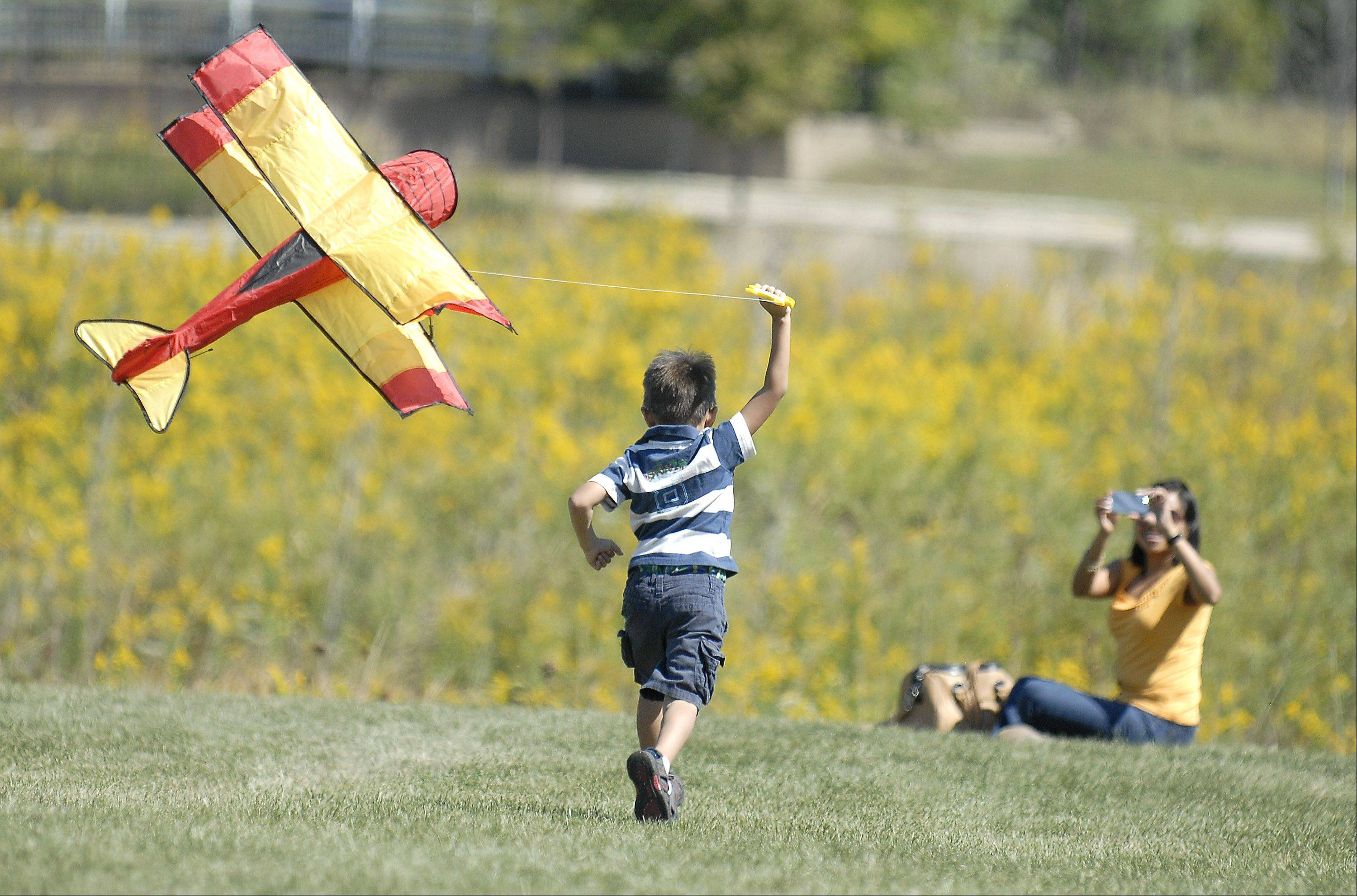 I saw a few kites hanging in the garage this week and it got me thinking about how much I'm looking forward to warm temps and bright summer colors. Then I remembered the fun and colorful photos I took during the last week of summer at the Geneva Park District's annual Kite Festival and thought I'd share. Tania Oldham of Geneva takes a photo of her son, Lucas, as his biplane kite soars at Peck Farm Park.