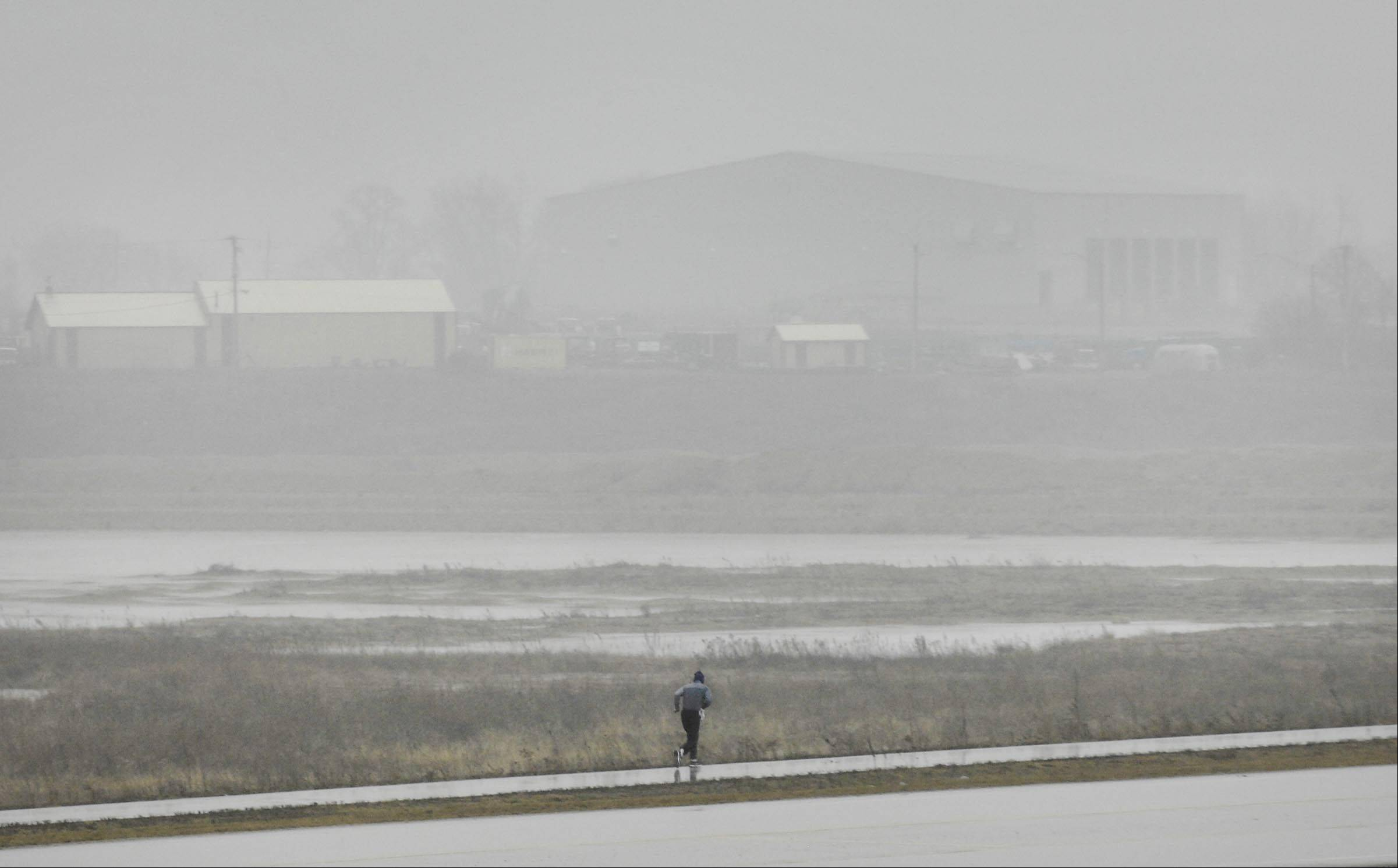 A jogger struggles through the rain on the Prairie Trail Tuesday afternoon near the Lake in the Hills Airport.