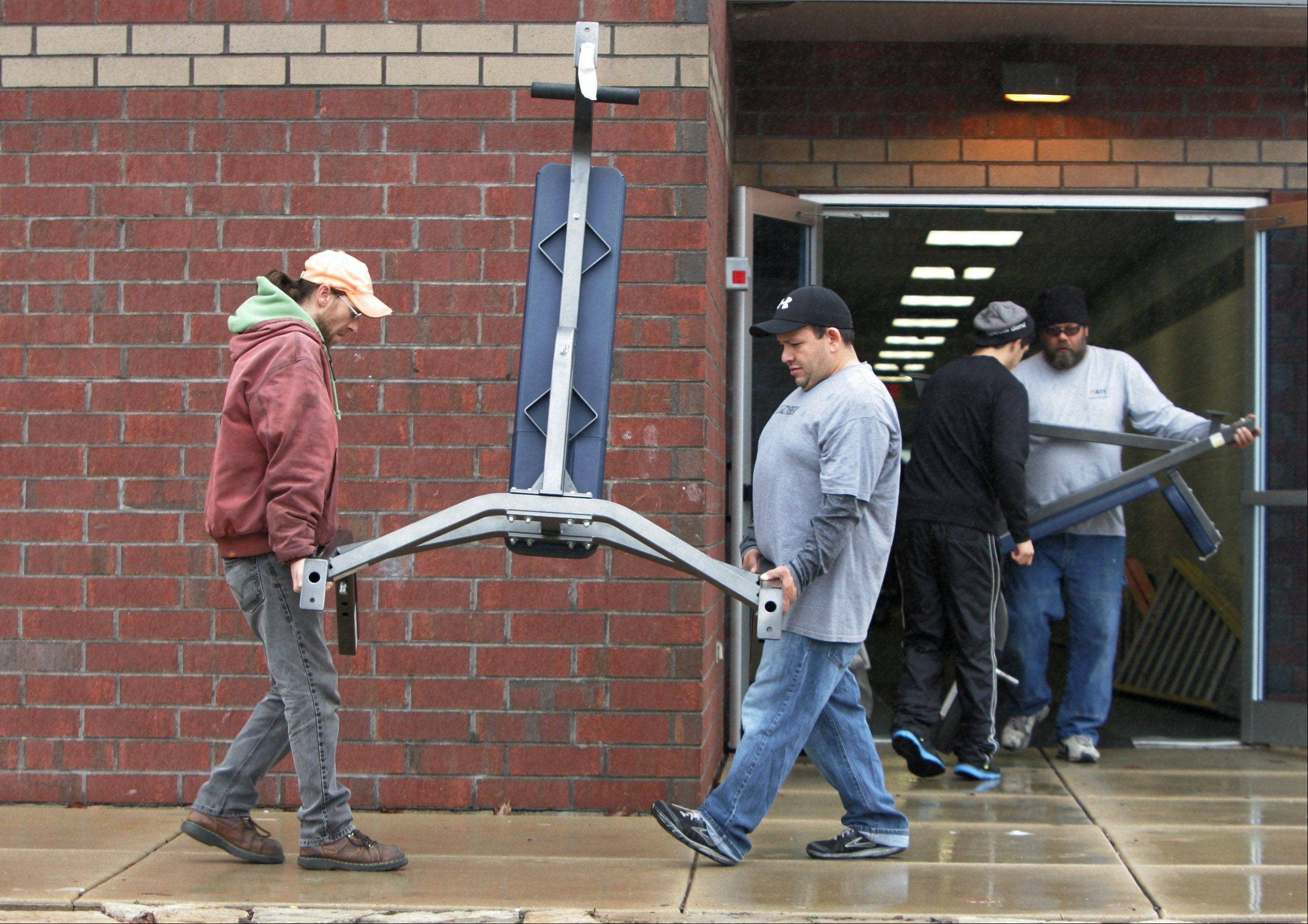 Fitness Equipment Services movers James Dunning, left, and Fernando Silva, remove exercise equipment from the New Lakeview Fitness Center Wednesday in Vernon Hills. The former YMCA closed last year and fitness equipment from the Vernon Hills Park District Sullivan Center will be moved to this site.
