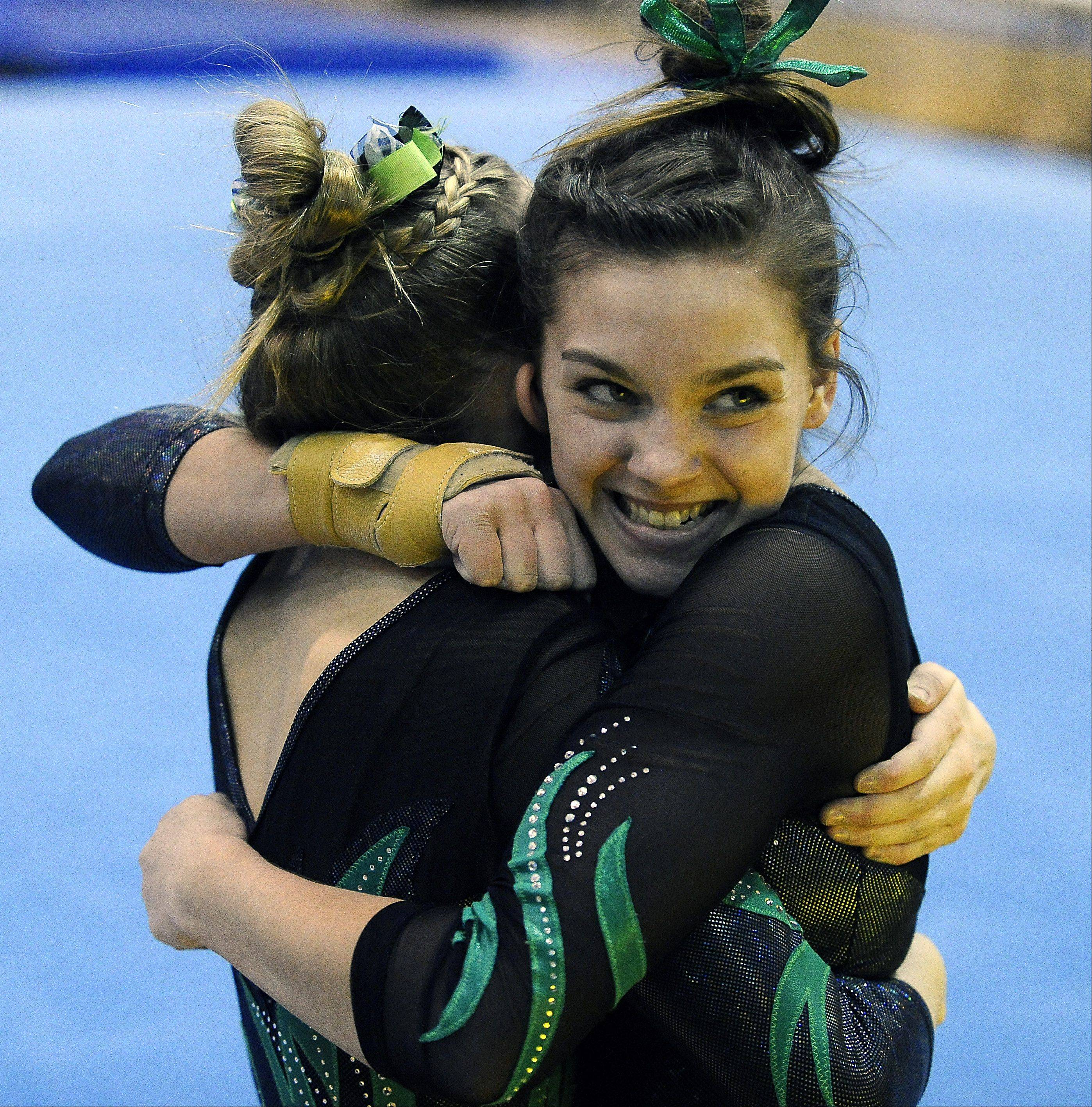 Fremd's Christine Radochonski gets hugs from her teammates after her floor exercise routine during sectional action Monday at Fremd.