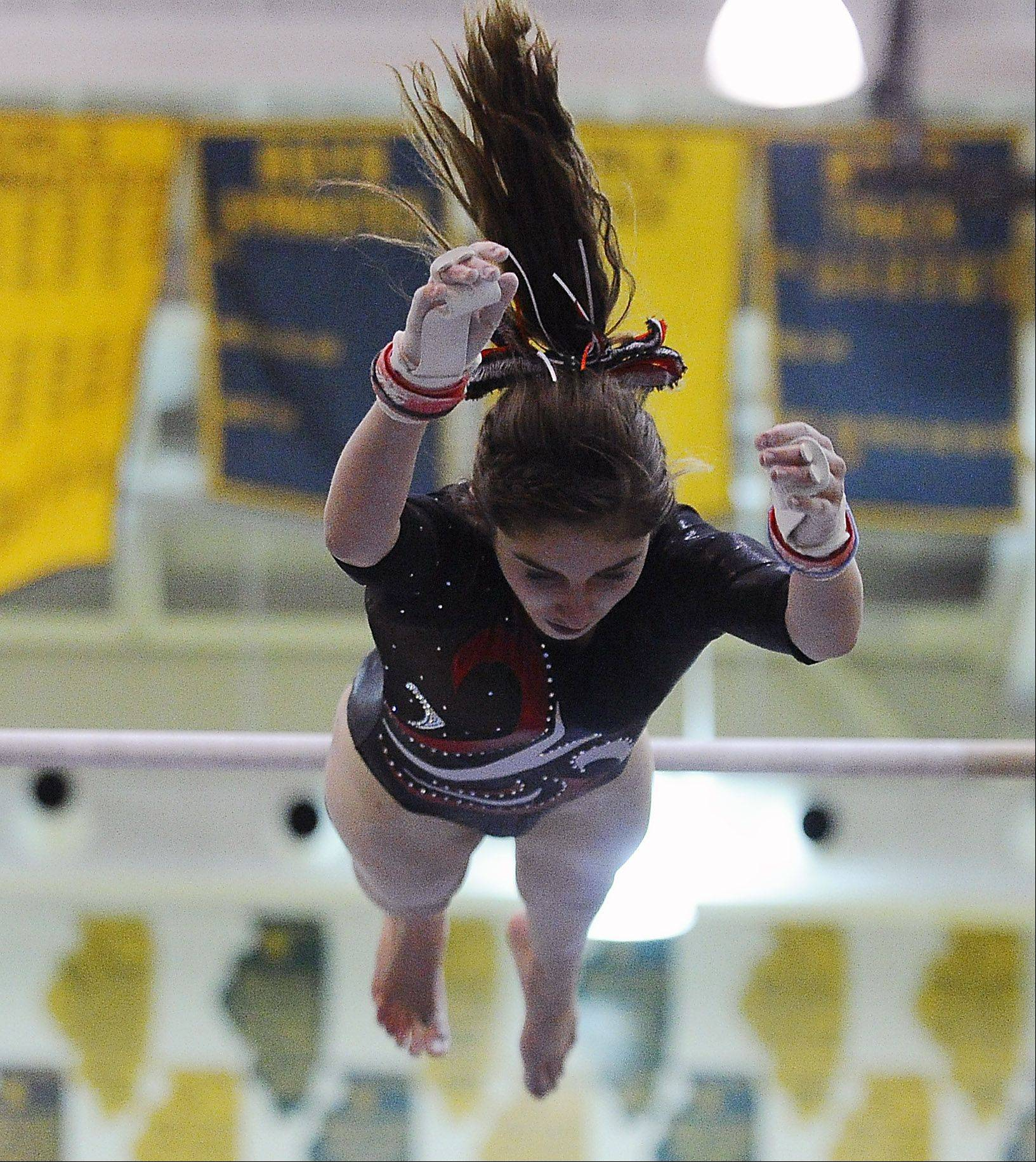 Palatine's Claudia Przystal is airborne during her dismount on uneven parallel bars during sectional action Monday at Fremd.