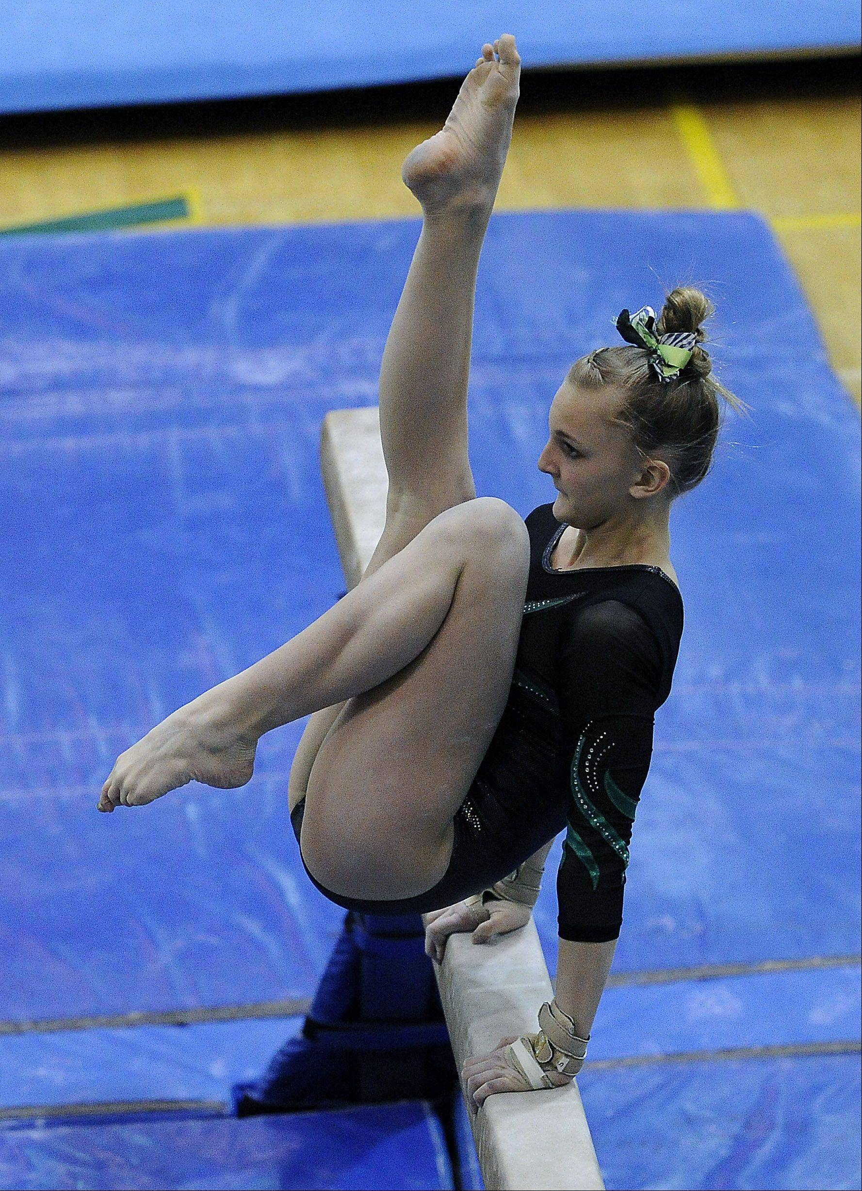 Fremd's Sydney Plichta works balance beam during sectional action Monday at Fremd.