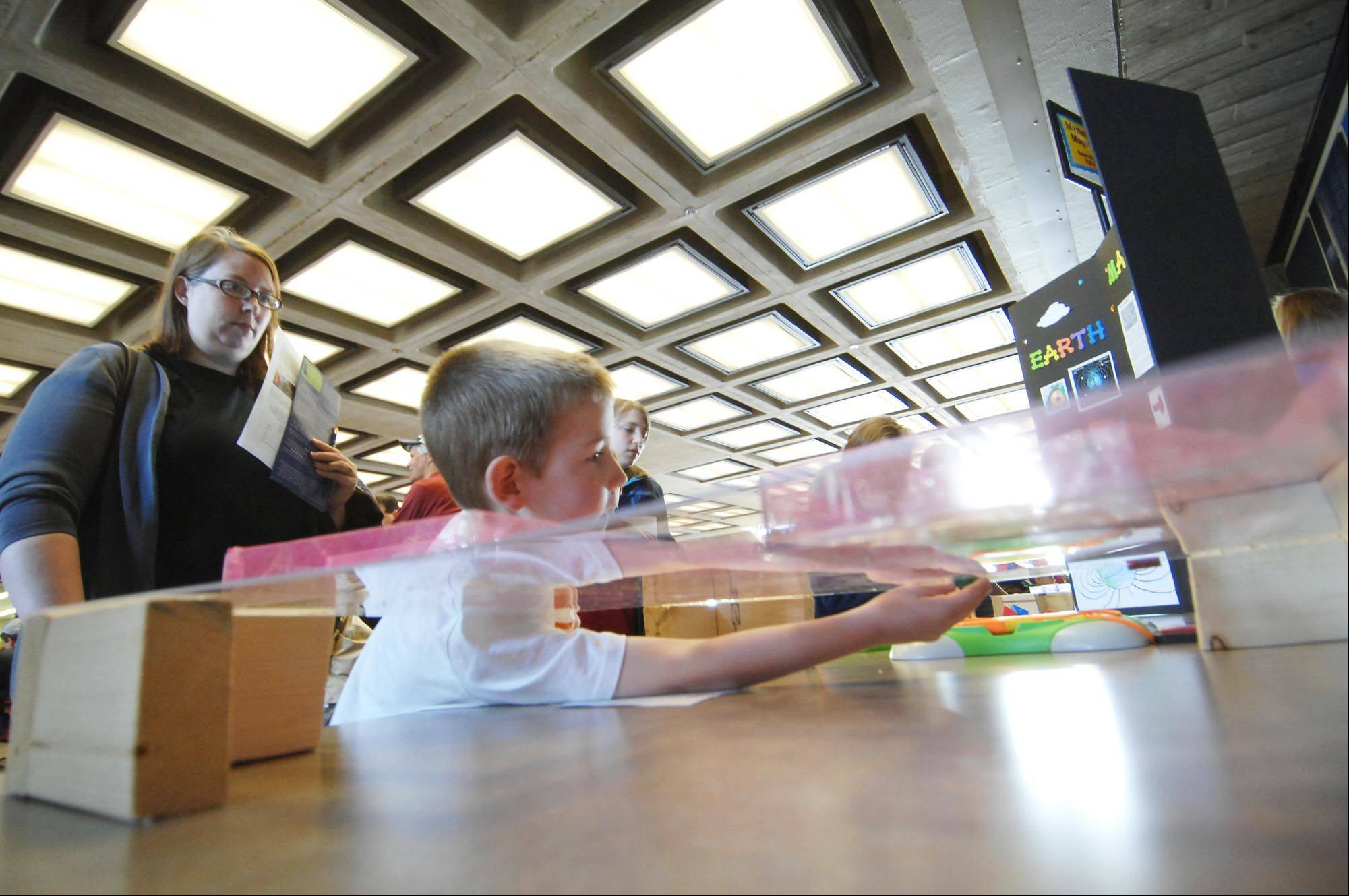 Henry Hanson of Gilberts reaches to guide a pair of magnets through a maze, created by Naperville Central High School students, during last year's Fermilab Family Open House in Batavia.