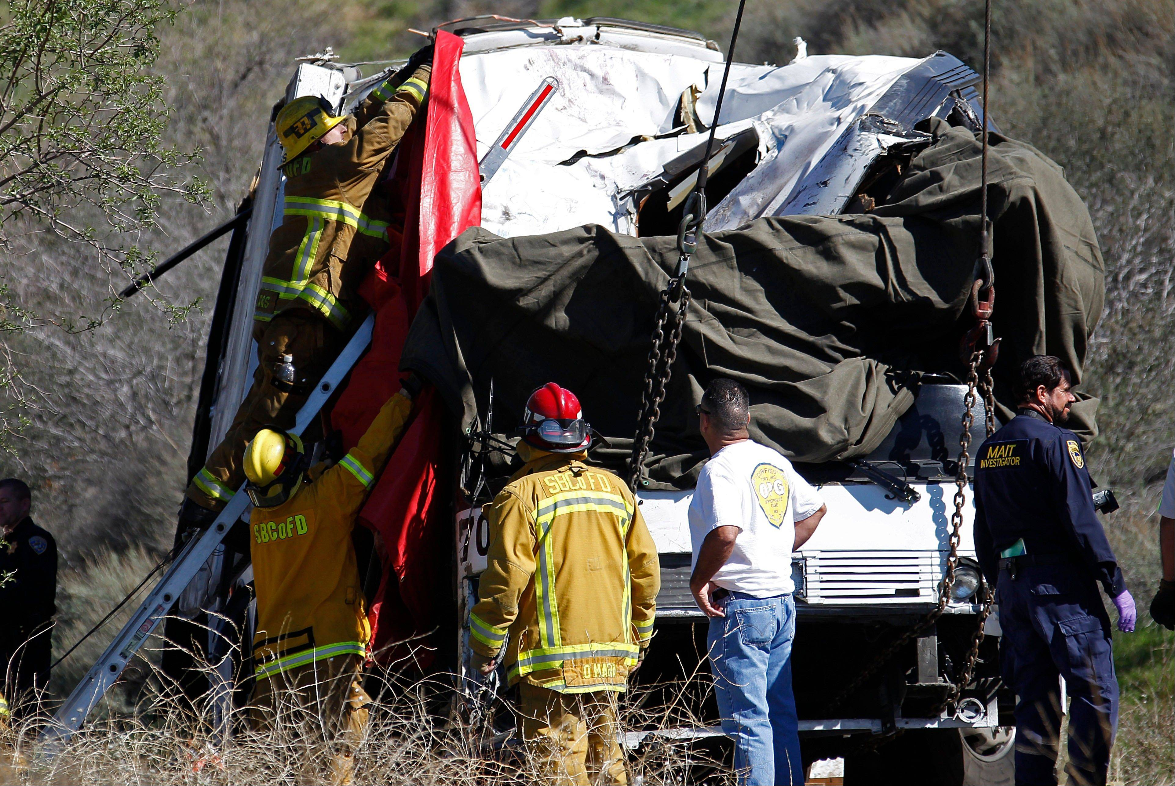 A firefighter adjusts a tarp to cover a victim inside after a tow truck lifted a tour bus back onto the road Monday, Feb. 4, 2013, after it collided with two other vehicles and crashed Sunday, killing at least eight people and injuring 38, on Highway 38 just north of Yucaipa, Calif. The bus was carrying a tour group from Tijuana, Mexico.