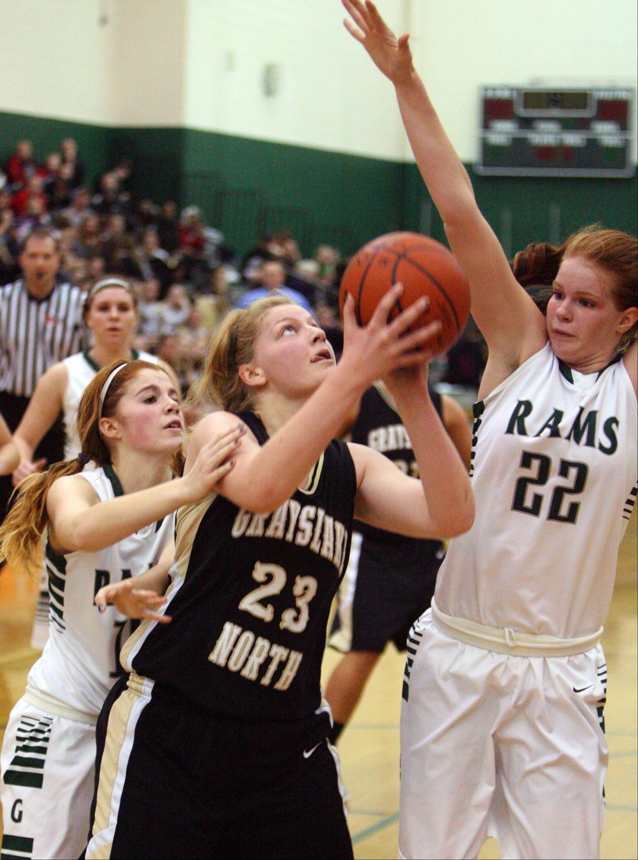 Grayslake North�s Joanna Guhl, center, drives past Grayslake Central�s Lauren Spaulding, left, and Morgan Dahlstrom on Tuesday night at Grayslake Central.