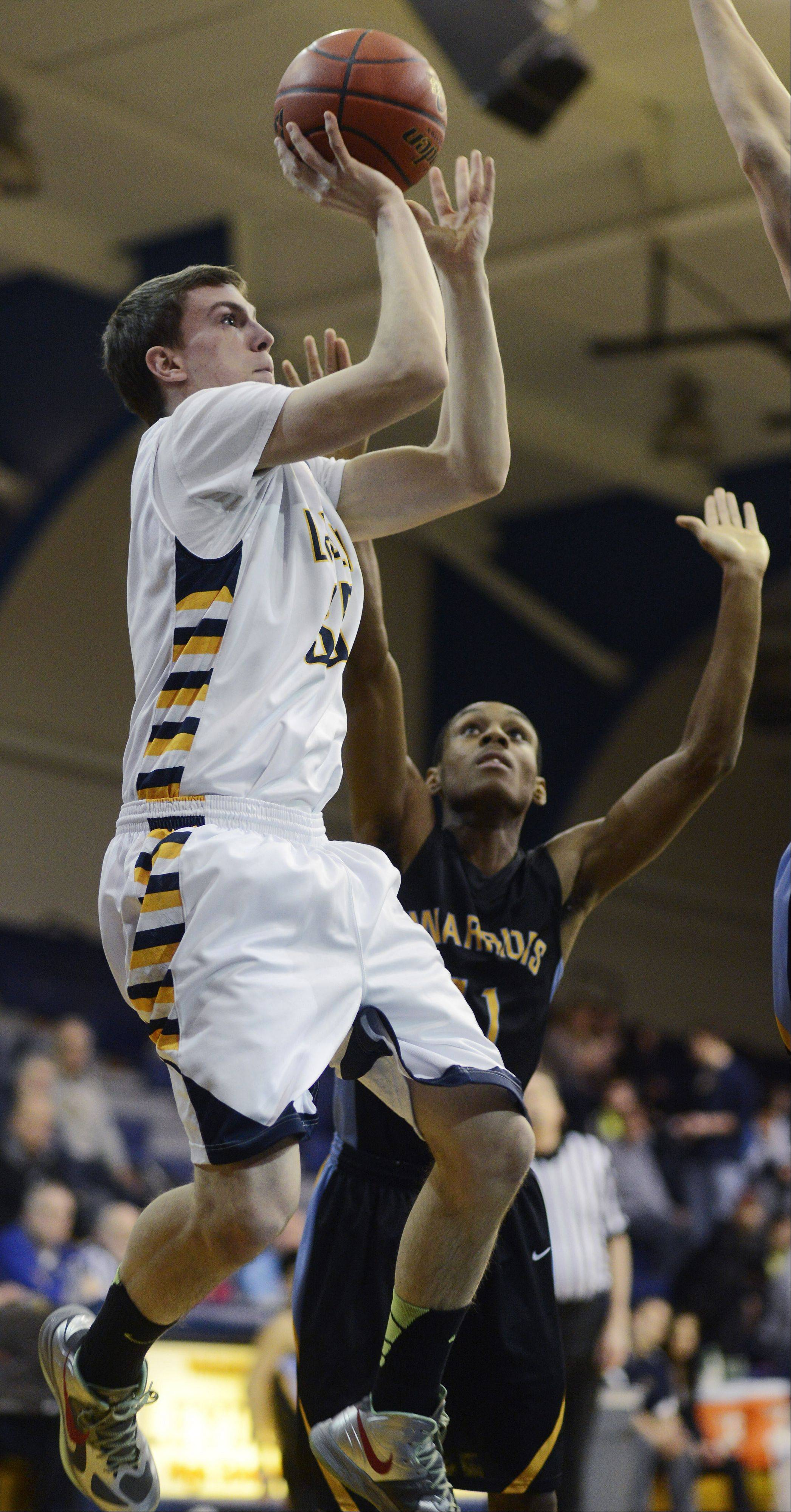 Leyden�s Jonny Woolf, left, takes a shot against the Maine West defense including Allante Bates.